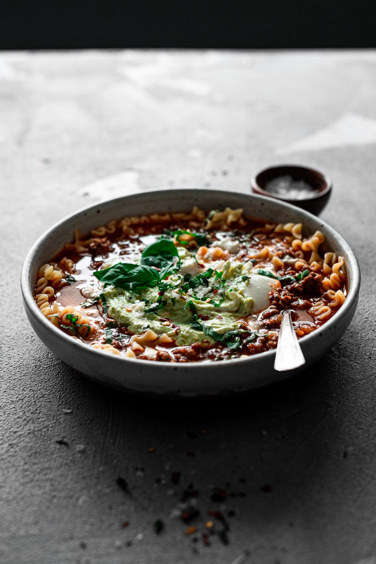 backlit bowl of lasagna soup with pesto ricotta