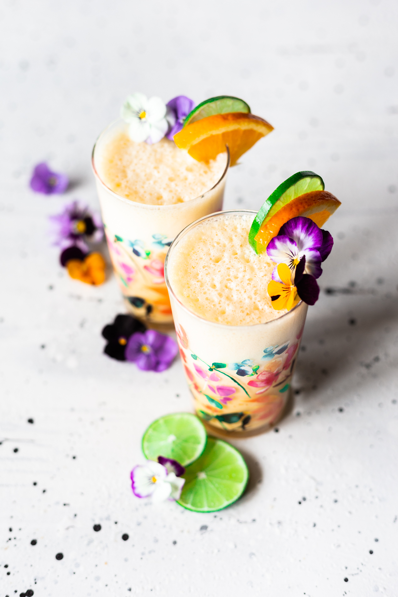 angled view of two glasses of homemade orange julius with orange and lime slices and fresh edible flowers