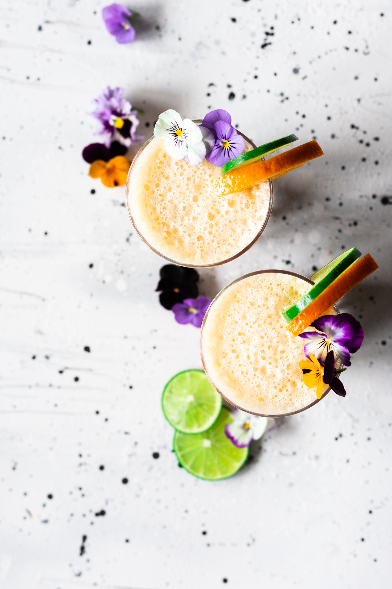 overhead view of two glasses of homemade orange julius with slices of orange and lime and fresh edible flowers