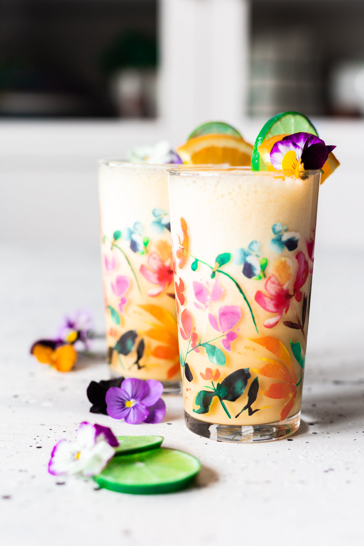 straight forward view of two glasses of homemade orange julius with slices of orange and lime and fresh edible flowers