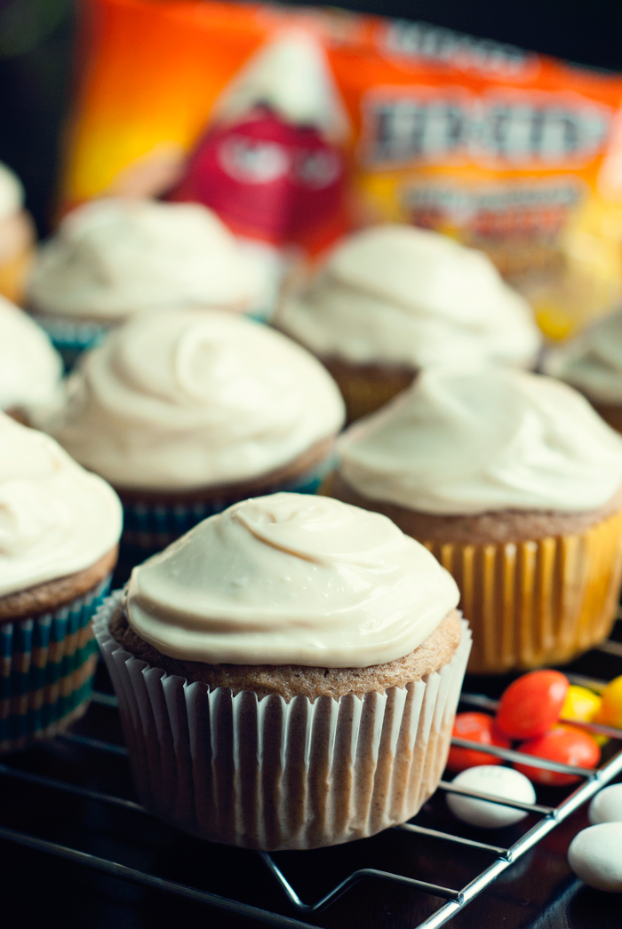 A close up view of a wire rack with spiced apple cupcakes on top in paper wrappers, topped with caramel cream cheese frosting. M&Ms are scattered below the rack to the right, and a bag is visible toward the back of the photo.