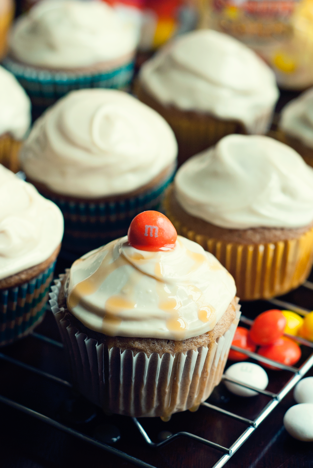 An angled close up view of a wire cooling rack with spiced apple cupcakes on top. Cupcakes are in paper wrappers and topped with caramel cream cheese frosting. The front cupcake has a caramel drizzle and a single M&M on top, while loose M&Ms are scattered below the wire rack to the right.