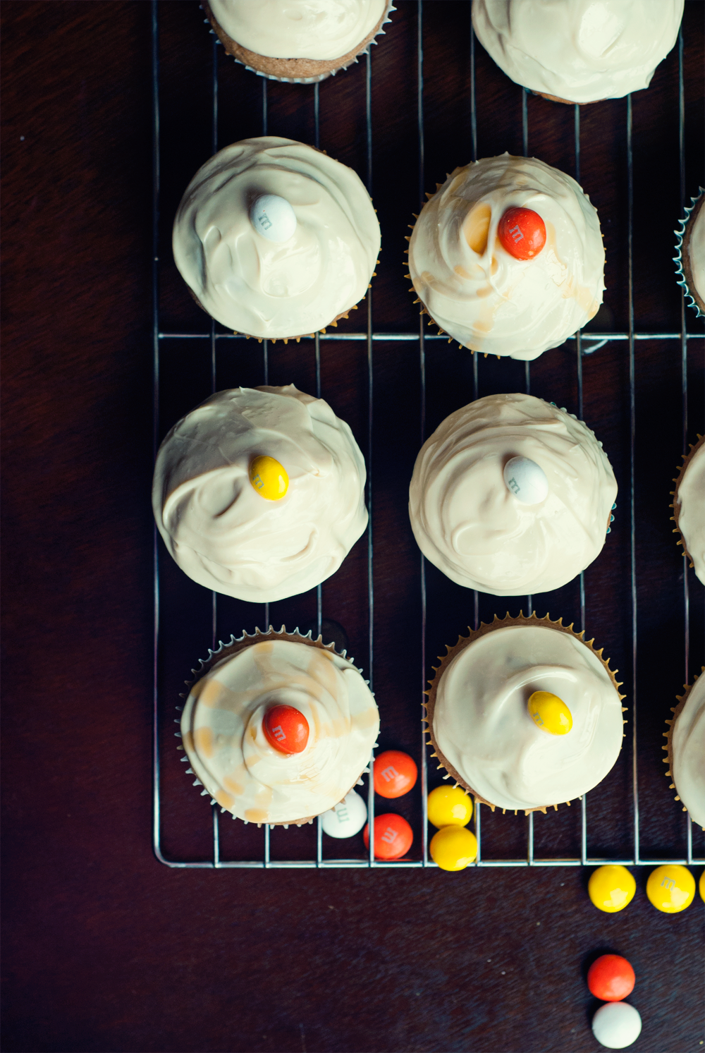 Overhead view of a wire rack, set to the right and top, with six spiced apple cupcakes fully visible, and another five running off the top and right side of the image. Cupcakes are topped with caramel cream cheese frosting and a couple have a caramel drizzle. All are topped with M&Ms and loose M&Ms are scattered to the bottom of the image and below the wire rack.