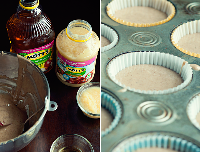 Two images: on the right is a close up view of a muffin tin with paper wrappers filled with spiced apple cupcake batter. On the left is a nearly empty mixing bowl of spiced apple cupcake batter, a jug of apple juice, a container of apple sauce, a small bowl of applesauce, and an empty glass bowl.