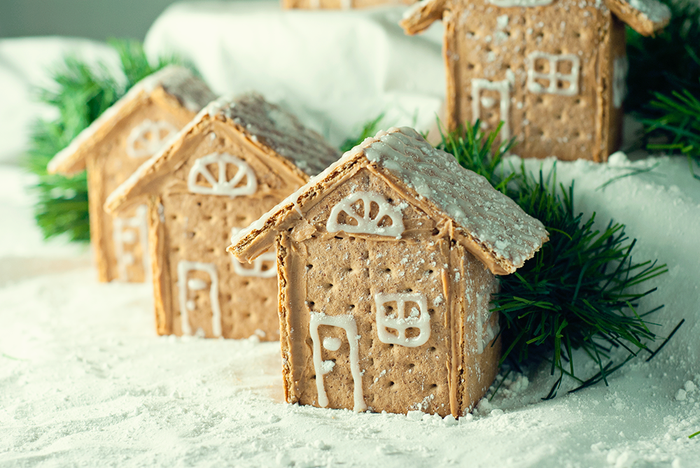 Gorgeous Graham Cracker House Village that is so easy to make with peanut butter and decorated with sparkle gel icing and powdered sugar!