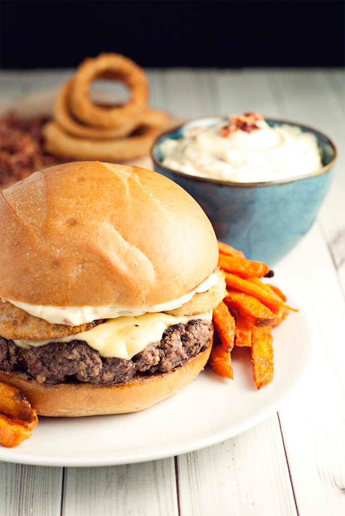 Game day has never been so delicious with this blackened pepper cheeseburger with onion rings and bacon aioli!
