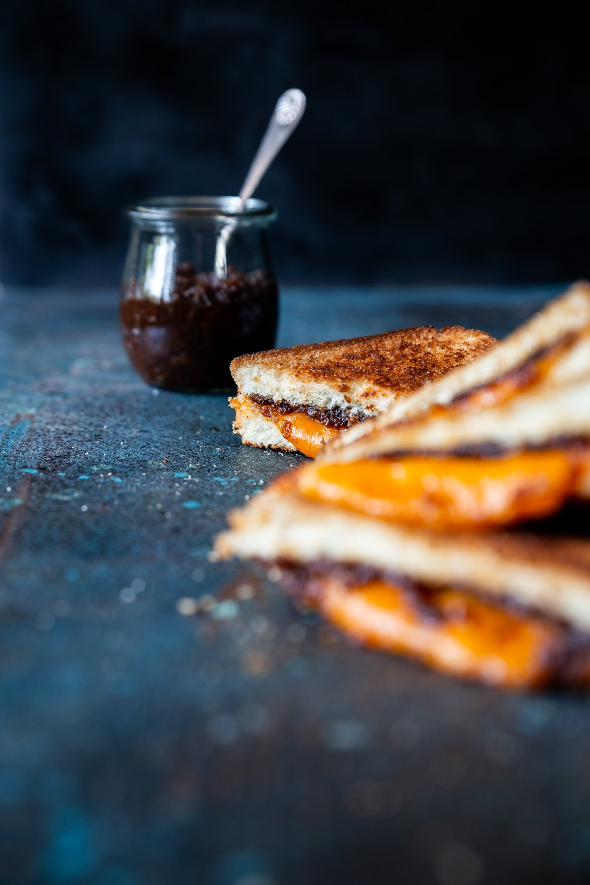 Bacon jam in small tulip jars, spoon with bacon jam on it, bacon jam grilled cheese triangles stacked on each other