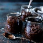 Bacon jam in small tulip jars, spoon with bacon jam on it