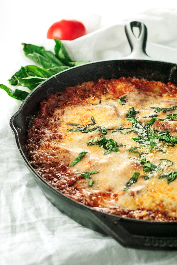 Cast iron skillet filled with cheesy lasagna