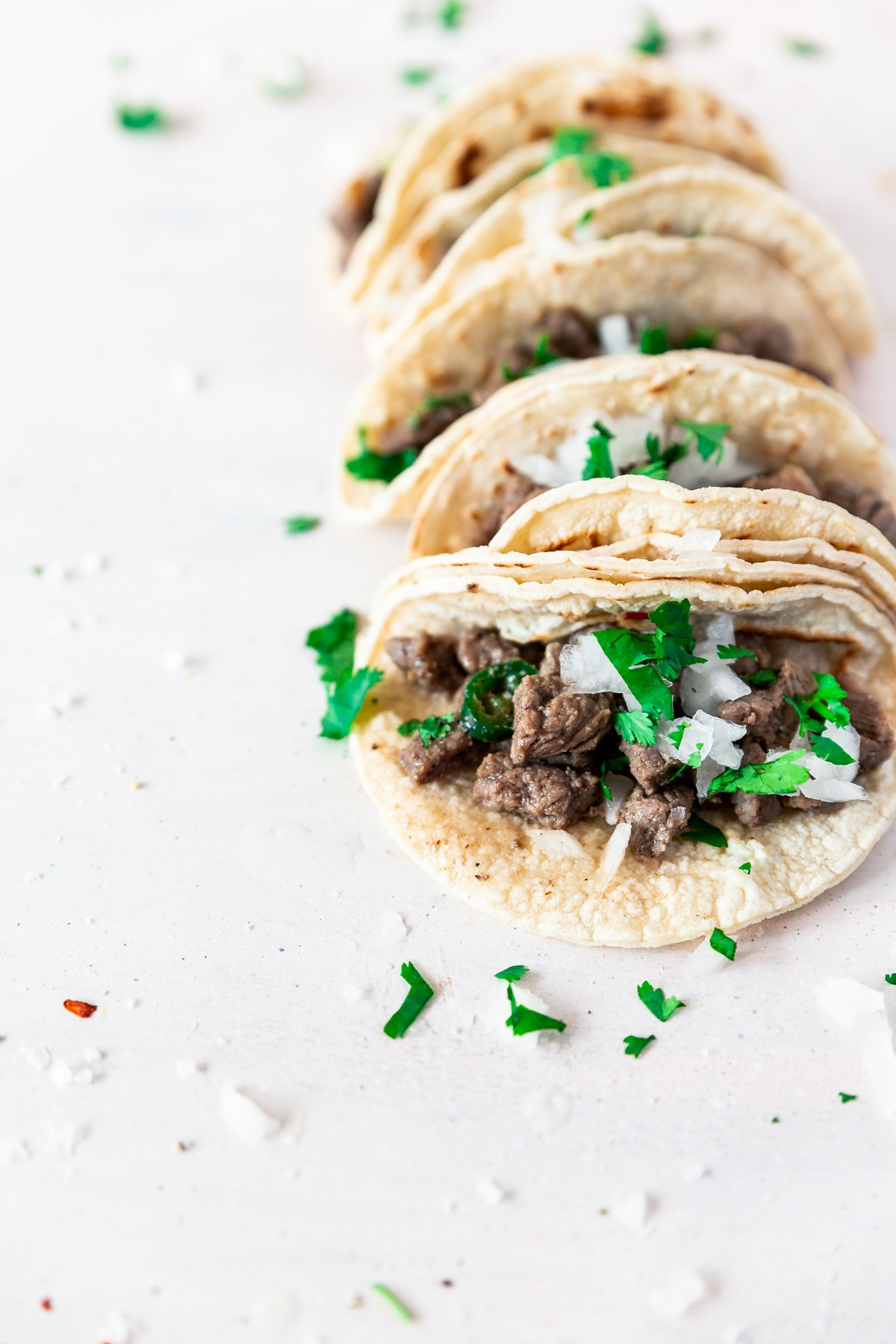 angled view of carne asada mexican street tacos with a double layer of corn tortillas sprinkled with cilantro and onion