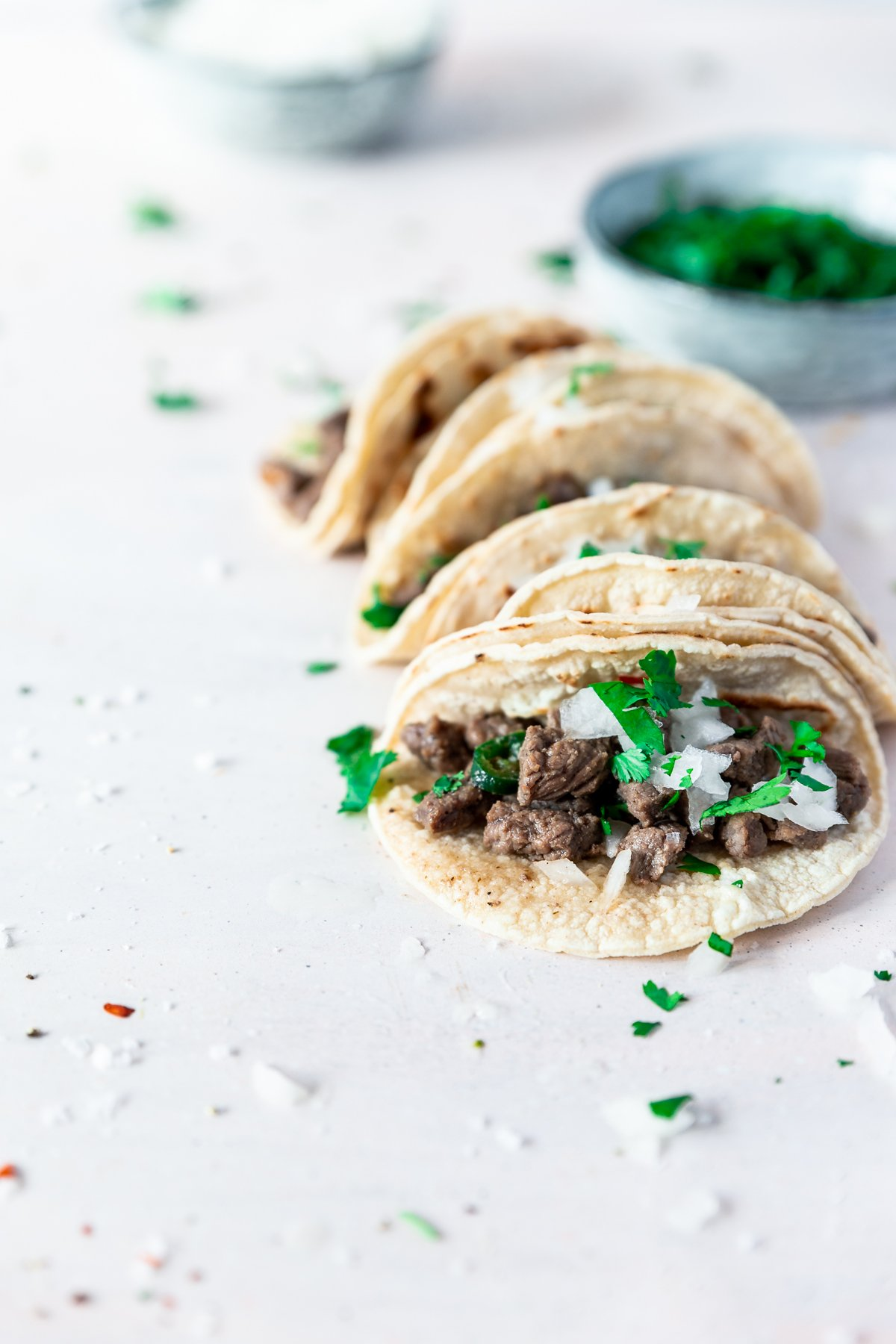 forty-five degree angle view of carne asada mexican street tacos sprinkled with onion and cilantro, aligned on the left side of the image. behind the easy mexican recipe is a bowl of cilantro and further back is a bowl of onion.