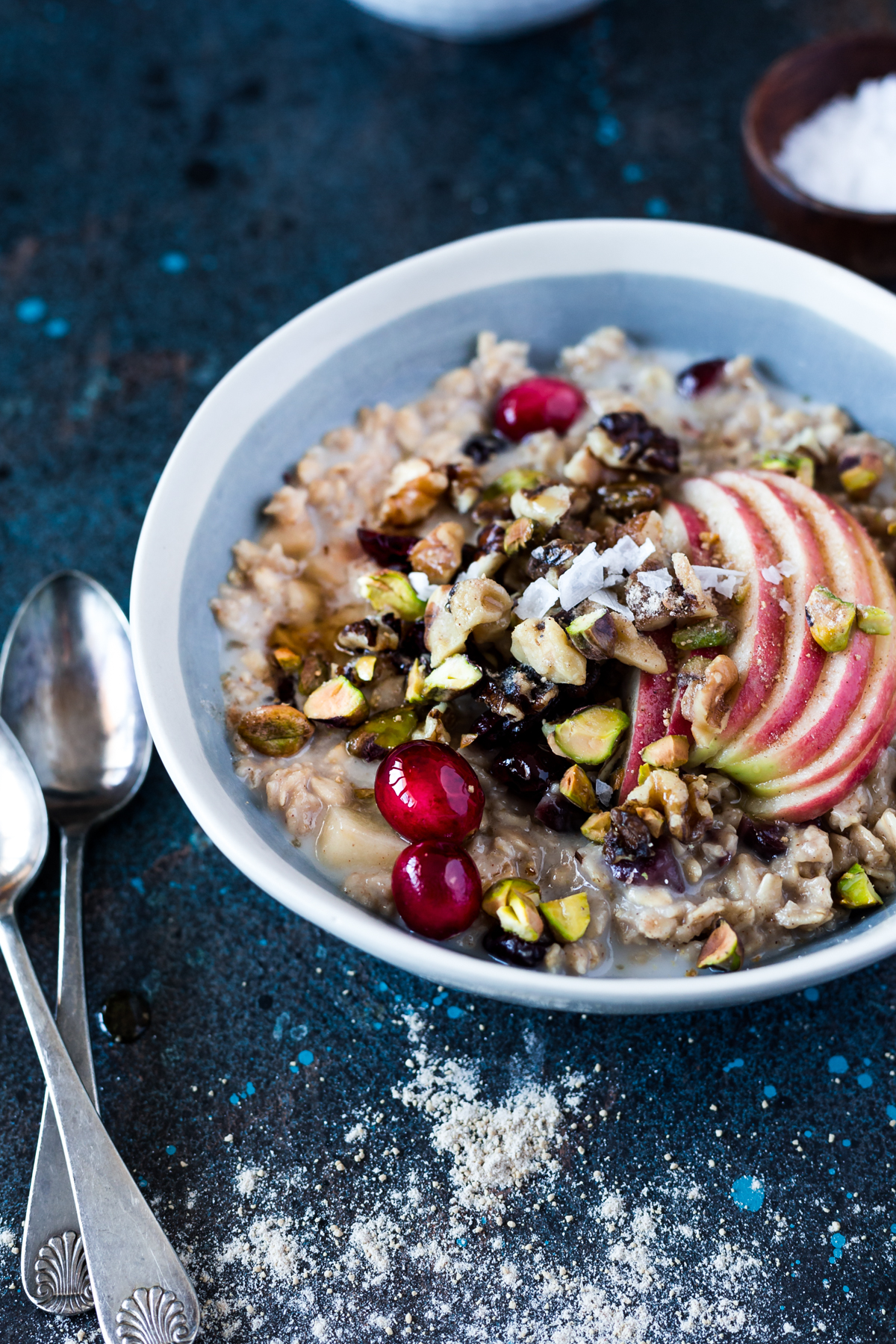 bowl of slow cooker warm apple and cranberry overnight oats topped with sliced apple, pistachios, walnuts, and fresh cranberries