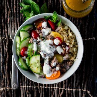 gluten free greek lamb bowls with cauliflower riced veggies, cucumbers, greek dressing, and tzatziki sauce