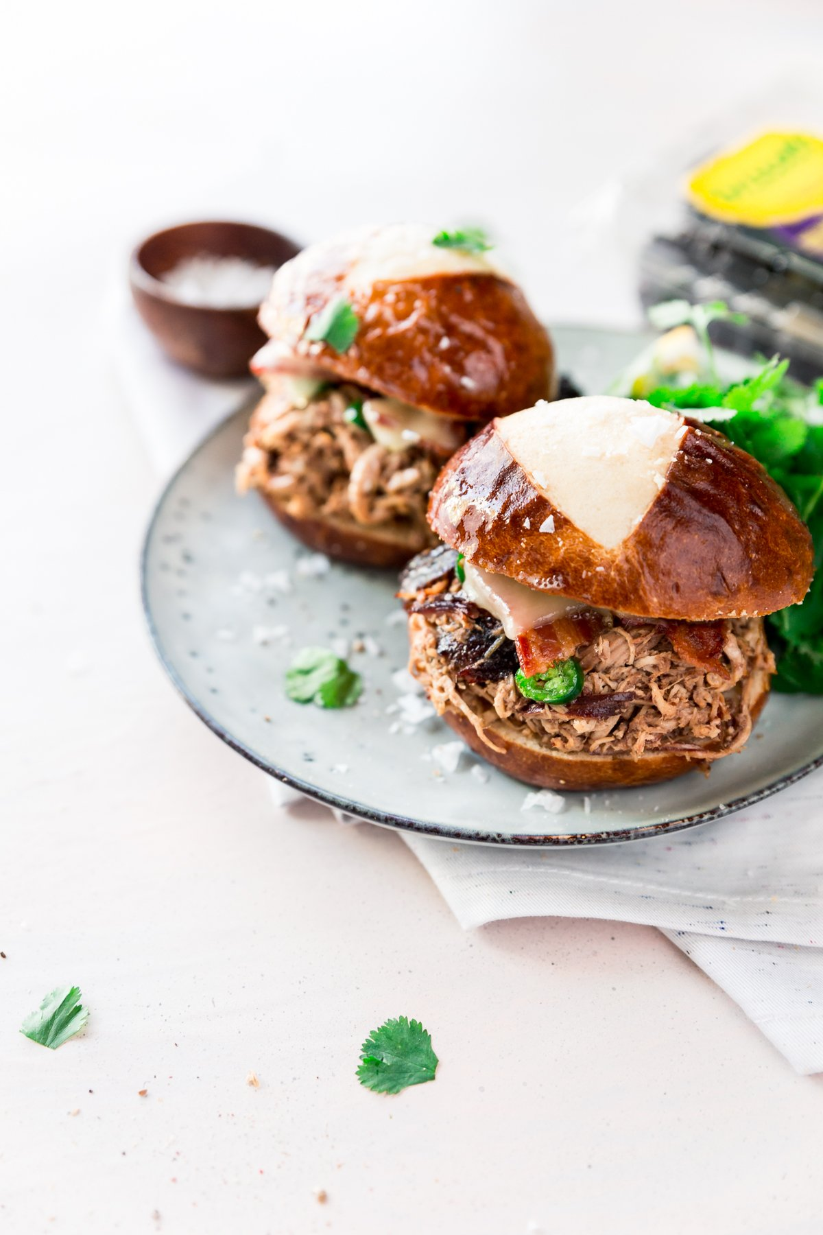 shredded chicken sliders with bacon and cheese on a small plate