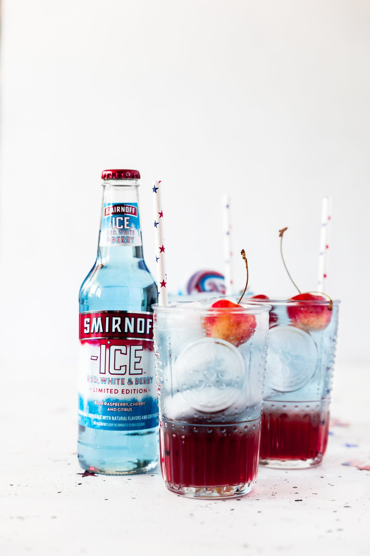 three glasses of cherries jubilee cocktail, red on bottom, blue on top, with fresh cherries, white paper straws with red and blue stars, bottle of Smirnoff ICE red white and berry