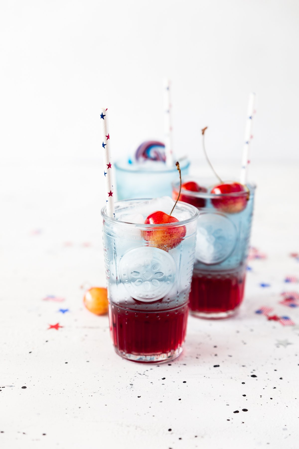 three glasses of cherries jubilee cocktail, red on bottom, blue on top, with fresh cherries, white paper straws with red and blue stars