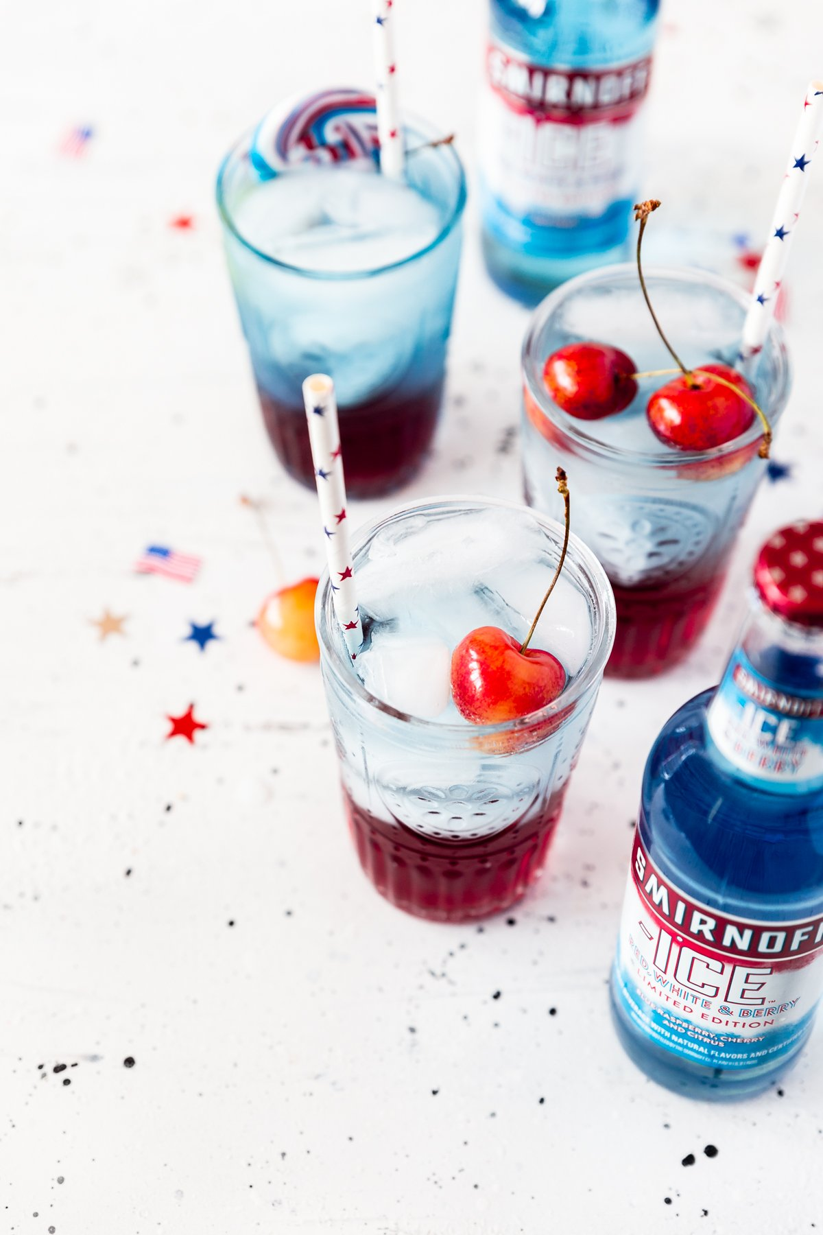 three glasses of cherries jubilee cocktail, red on bottom, blue on top, with fresh cherries, white paper straws with red and blue stars, 2 bottles of Smirnoff ICE red white and berry
