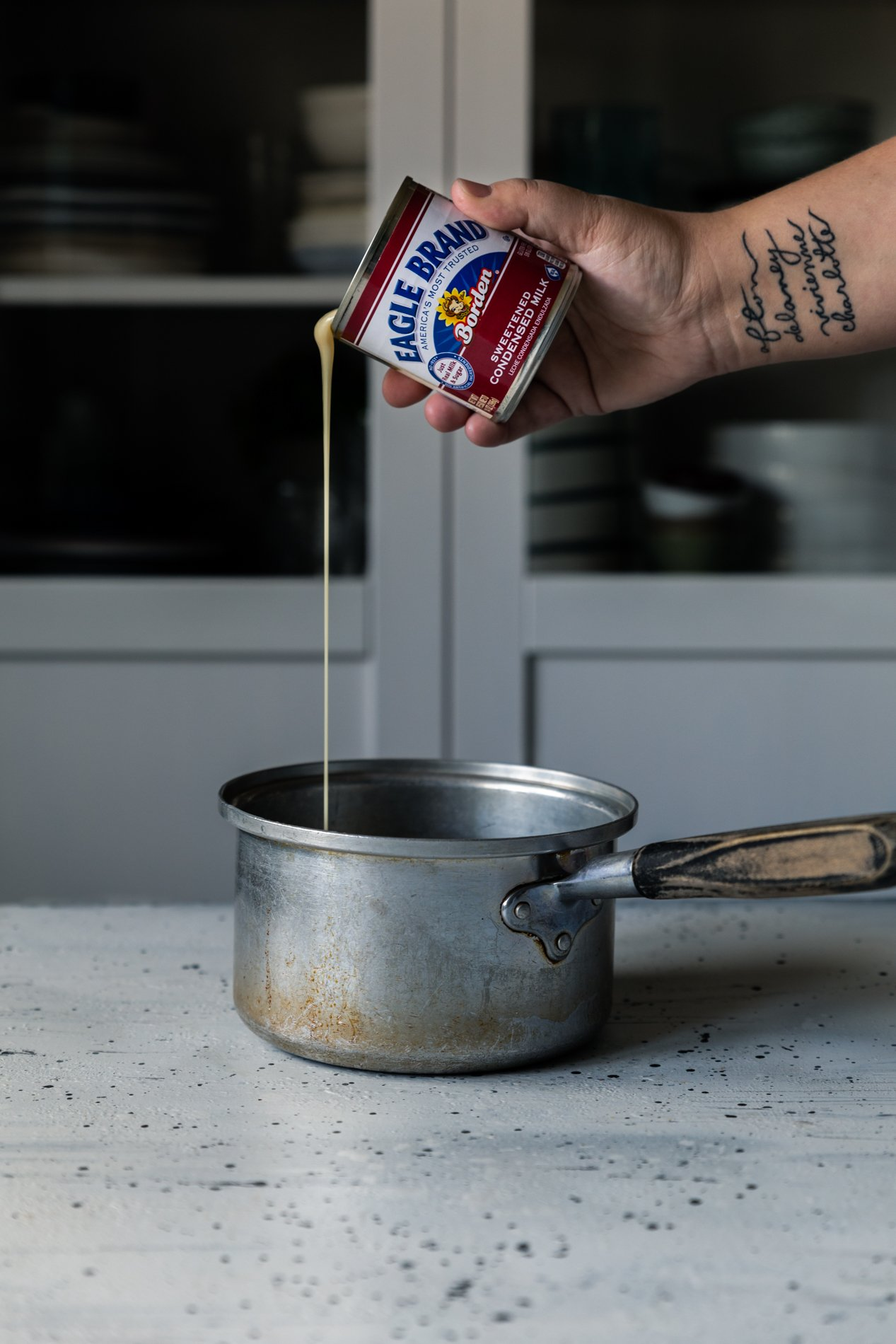 A vintage metal pot sits just below center of the image, with eagle brand sweetened condensed milk being poured into it from six inches above the pot. a hand and forearm are present in the shot, with tattoos on the inner wrist visible.