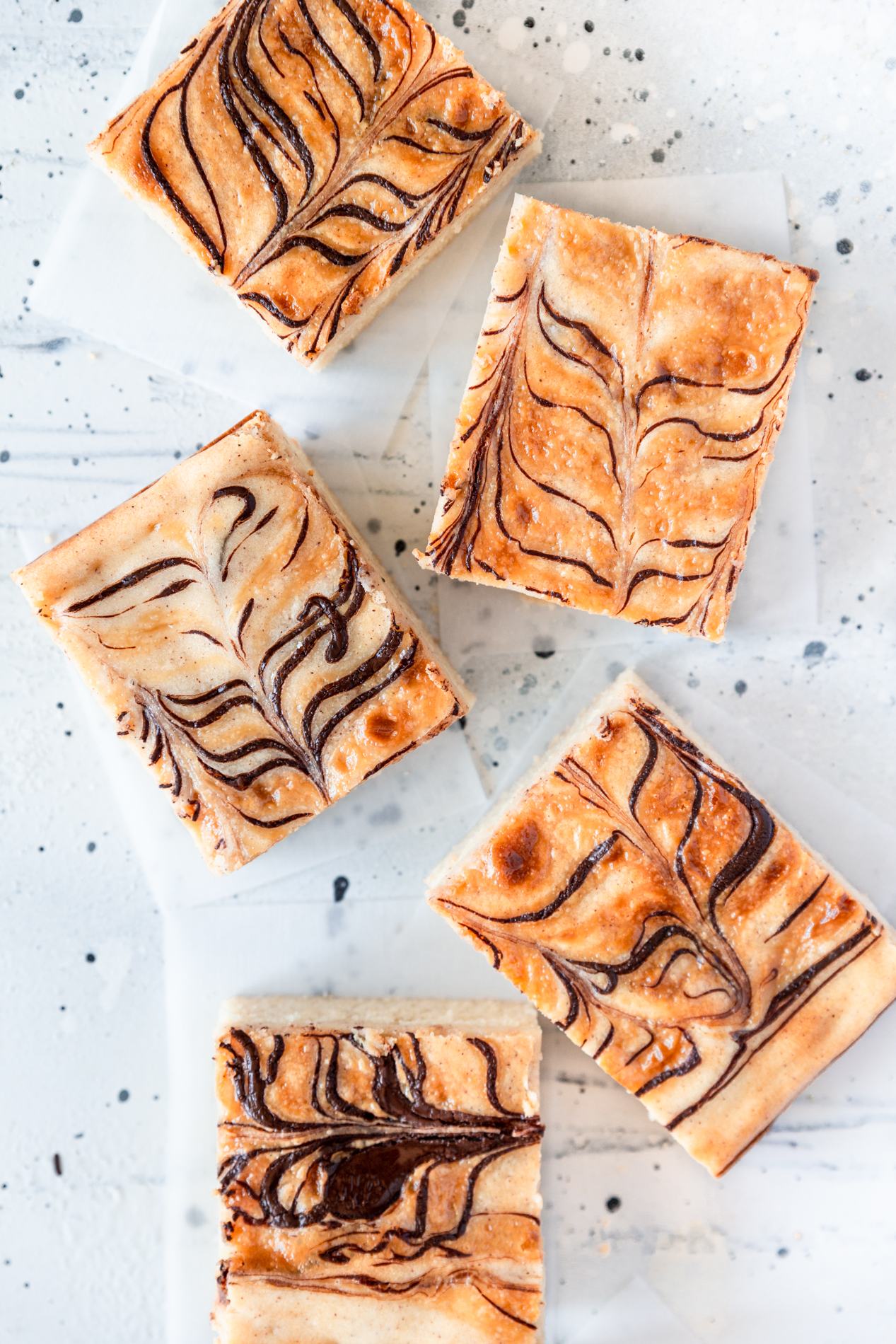 overhead view of five slices of churro cheesecake cookie bars with dulce de leche and dark chocolate ribbons, on parchment paper squares.