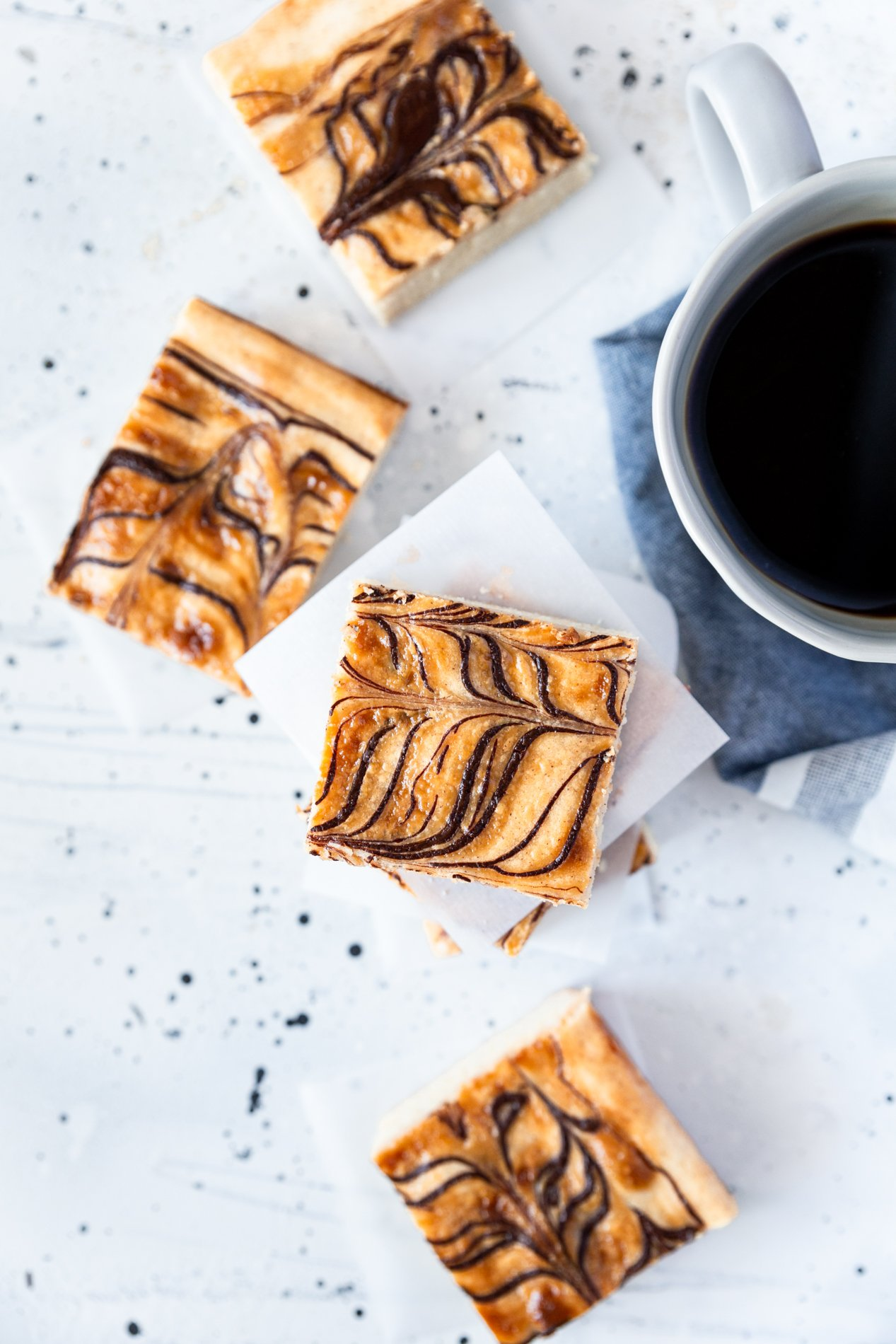 overhead view of churro cheesecake cookie bars with dulce de leche and dark chocolate ribbons. there are four slices on a white background and one of the slices is stacked with extra bars. a cup of coffee sits partially off-image to the right, on top of a blue cloth.