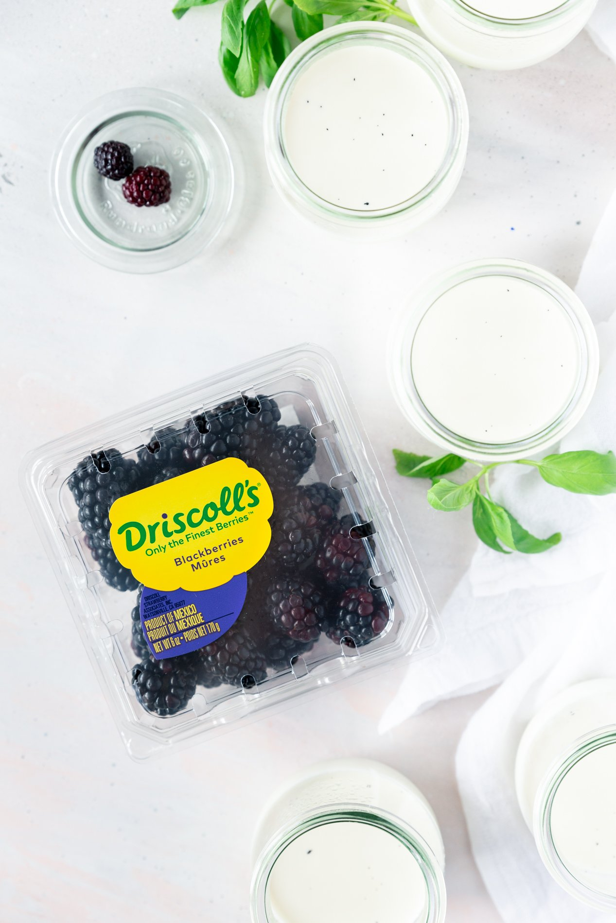 overhead view of jars of vanilla bean panna cotta, surrounded by fresh basil leaves with a container of Driscoll's blackberries.
