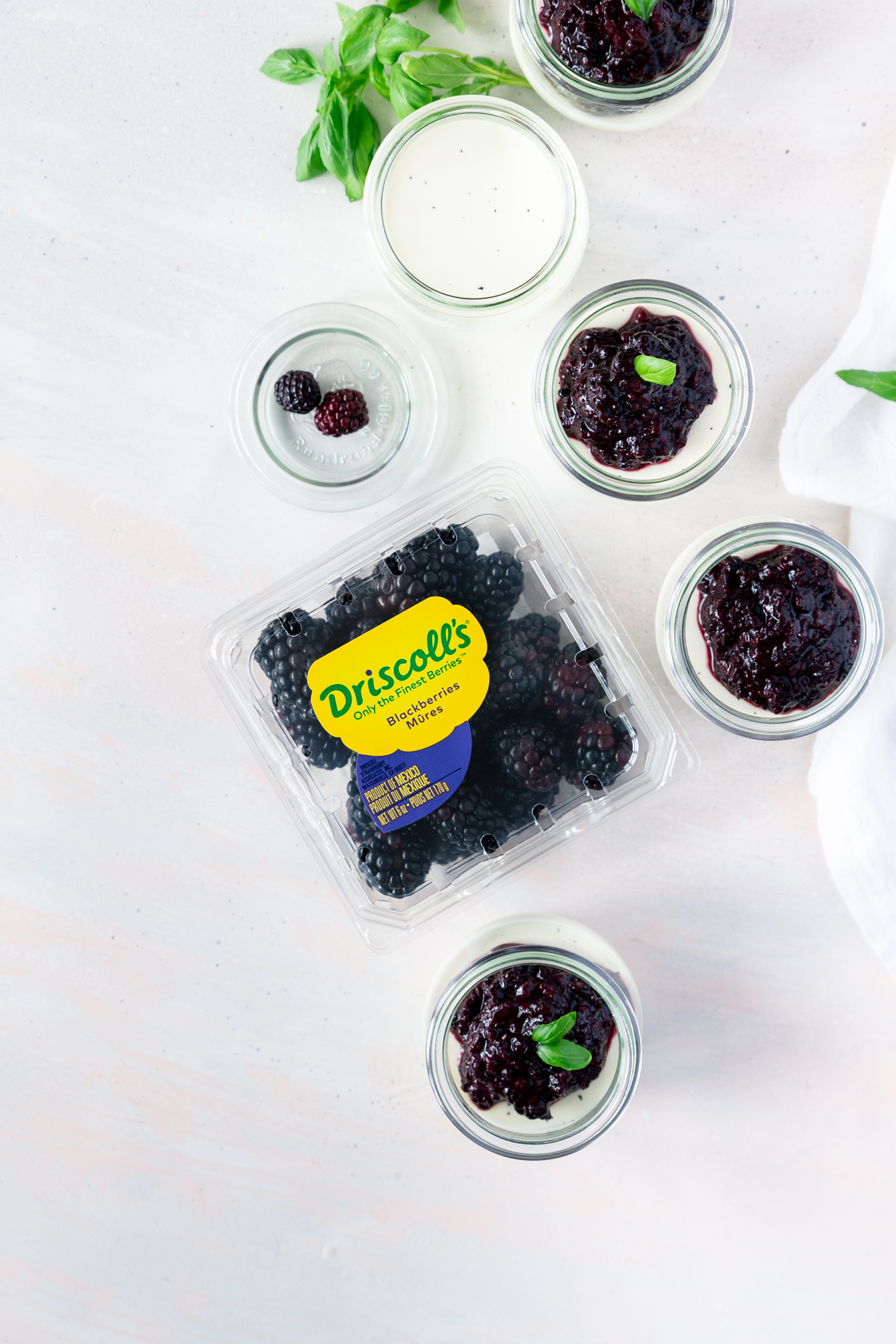 overhead view of jars of vanilla bean panna cotta with basil blackberry compote, surrounded by fresh basil leaves and a container of Driscoll's blackberries.