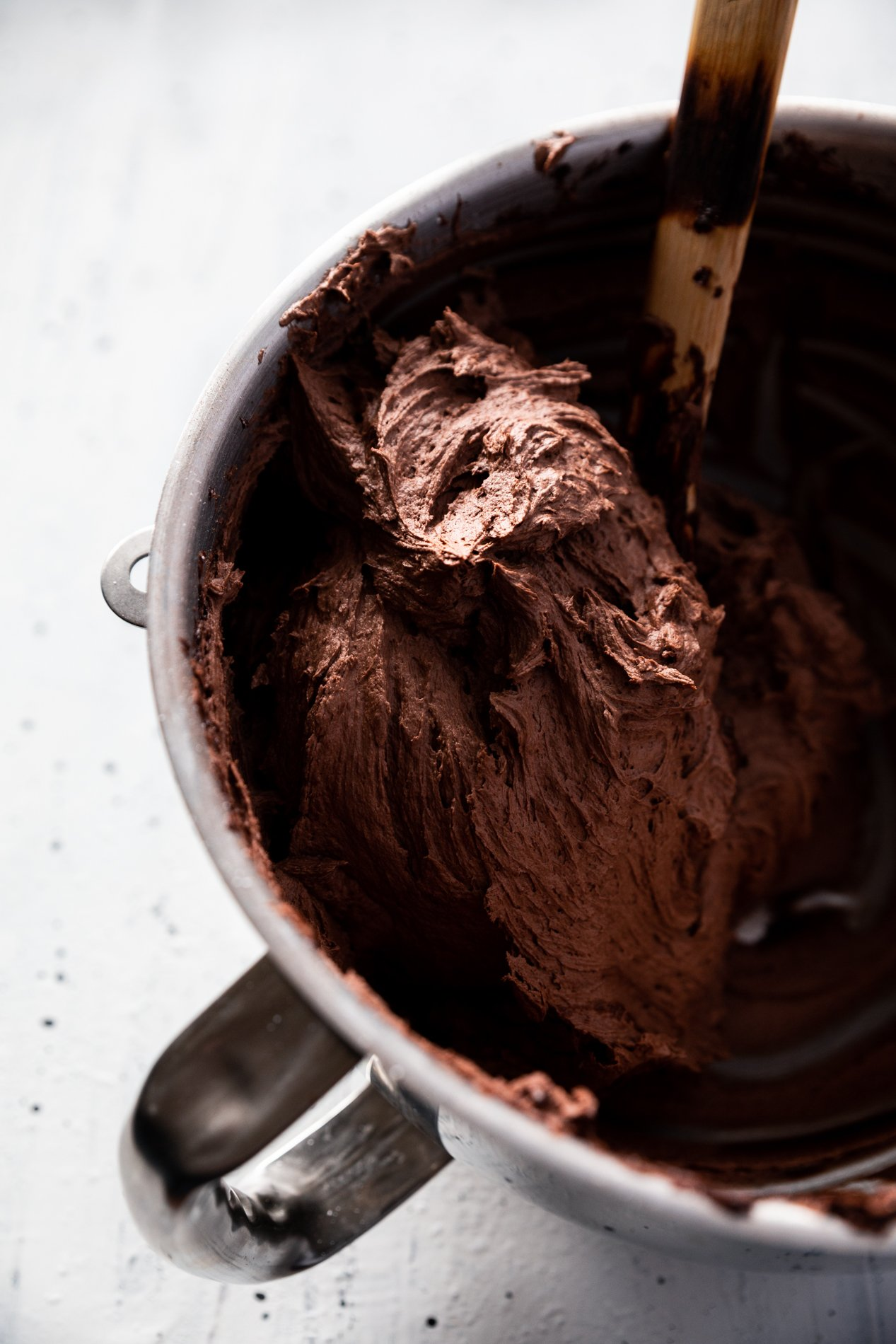 big bowl of chocolate frosting with a spoon inside it.