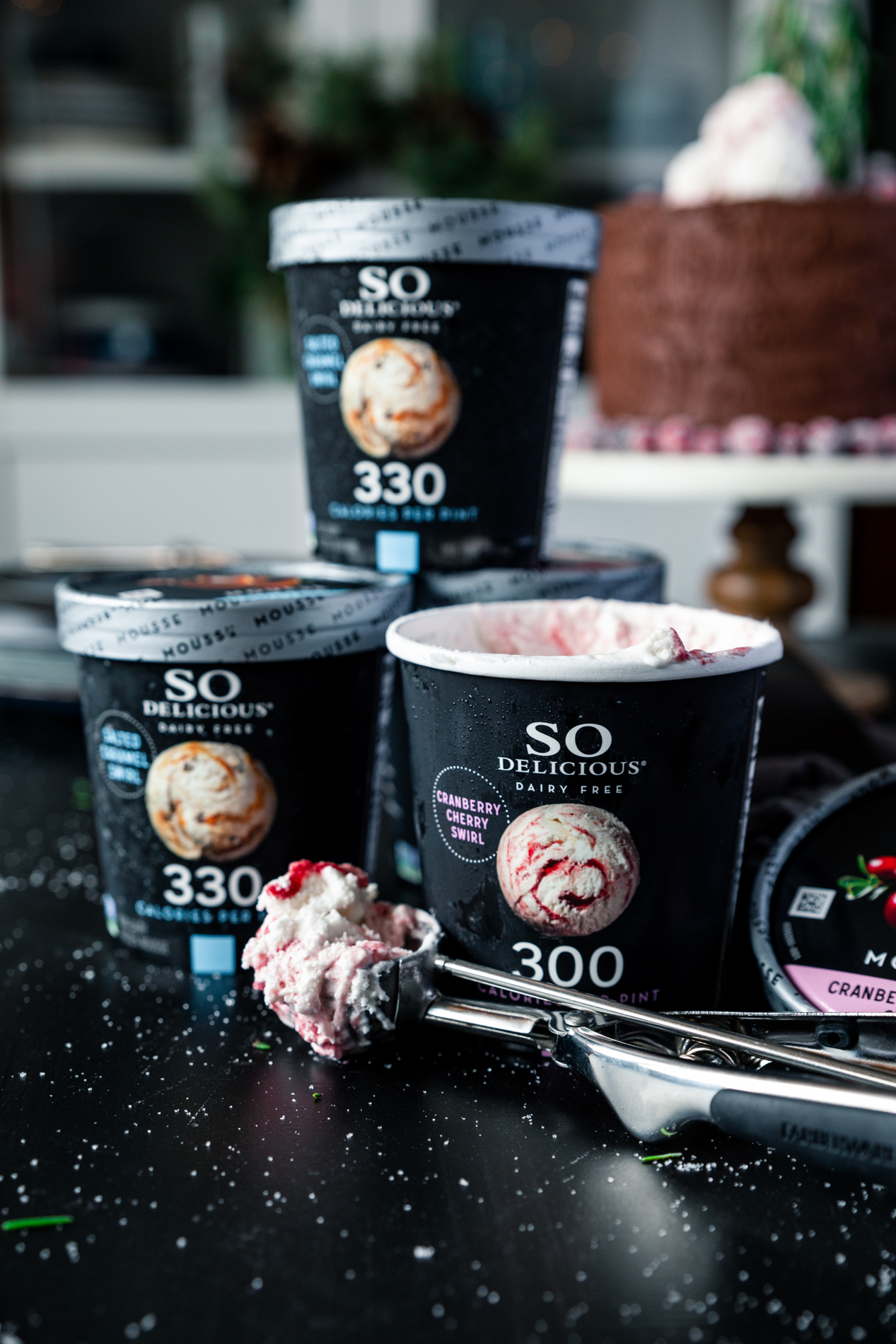 straight forward view of pints of SO Delicious Dairy Free Frozen Mousse in Cranberry Cherry Swirl and Salted Caramel Swirl, with a double chocolate tree stump cake in the background.