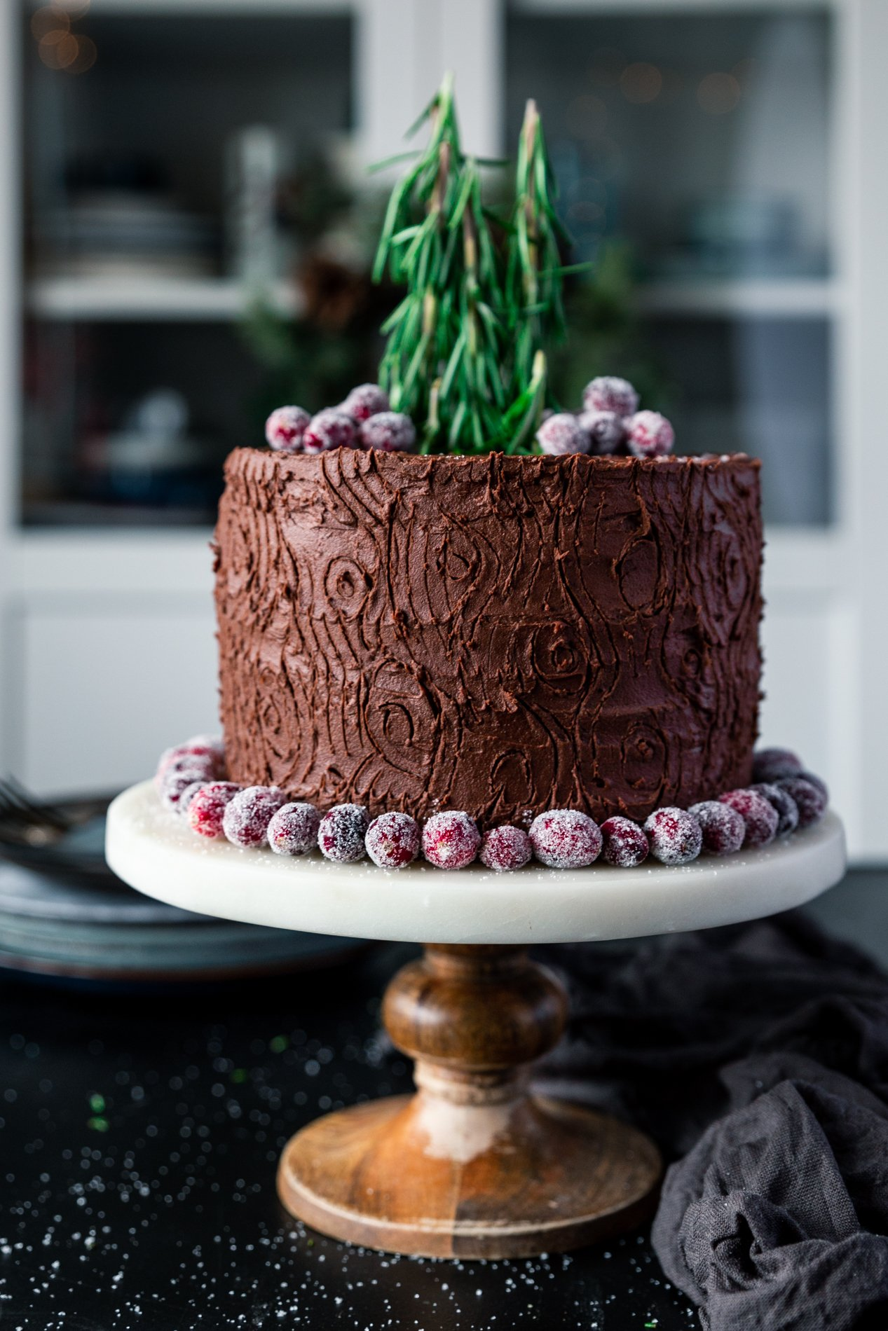 straight-forward view of a chocolate cake on a cake stand with a tree stump design, surrounded by sugared cranberries, with sugared cranberries on top and rosemary sprigs acting as trees.