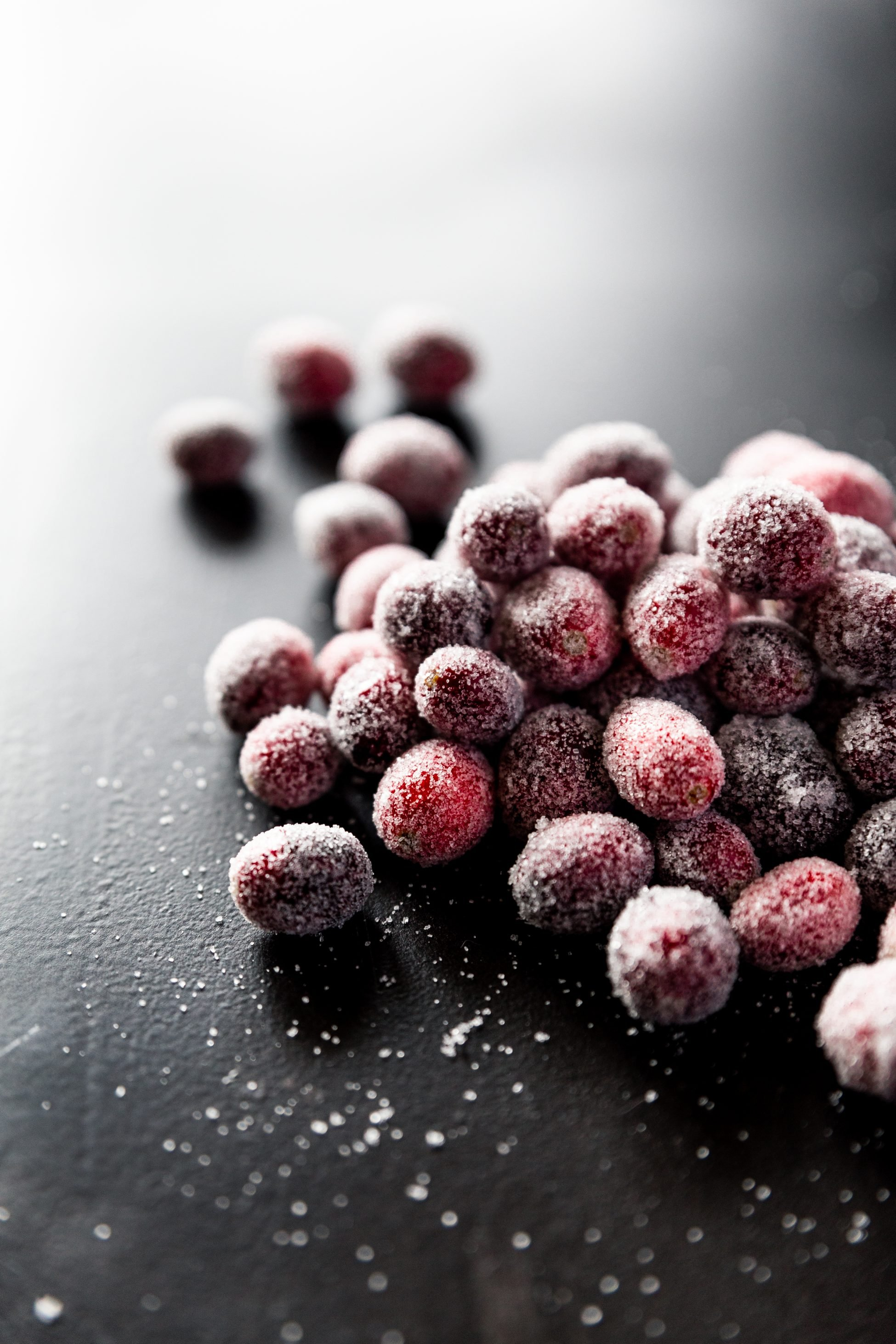 forty-five degree angled view of a pile of sugared cranberries on a black surface.