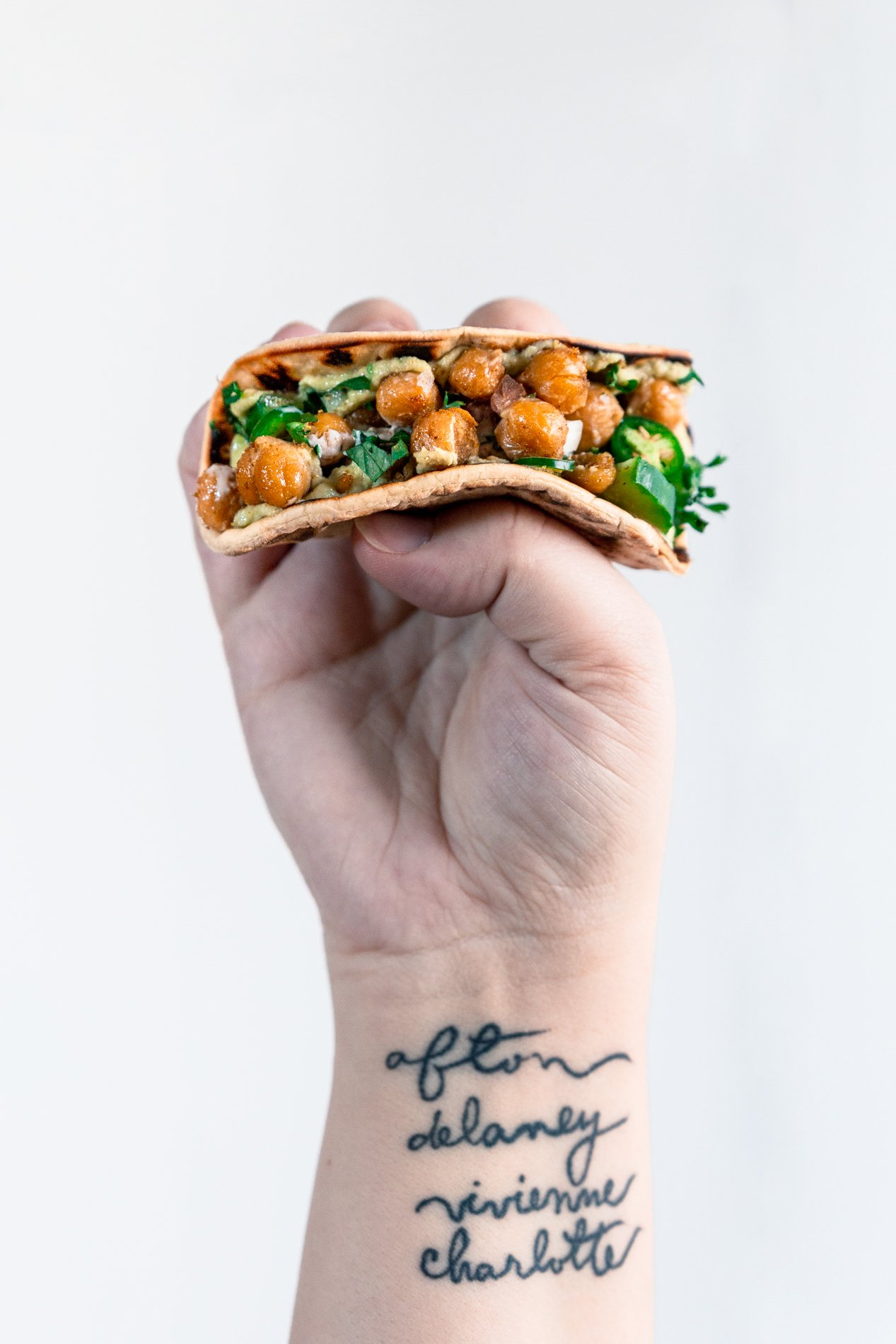 view of a forearm holding a deconstructed falafel pita taco.