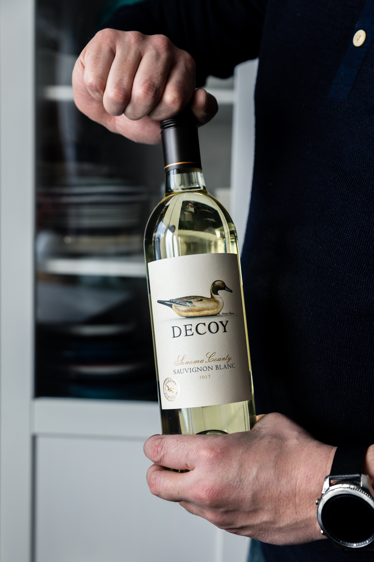 View of a man opening a bottle of Decoy Wine Sauvignon Blanc.