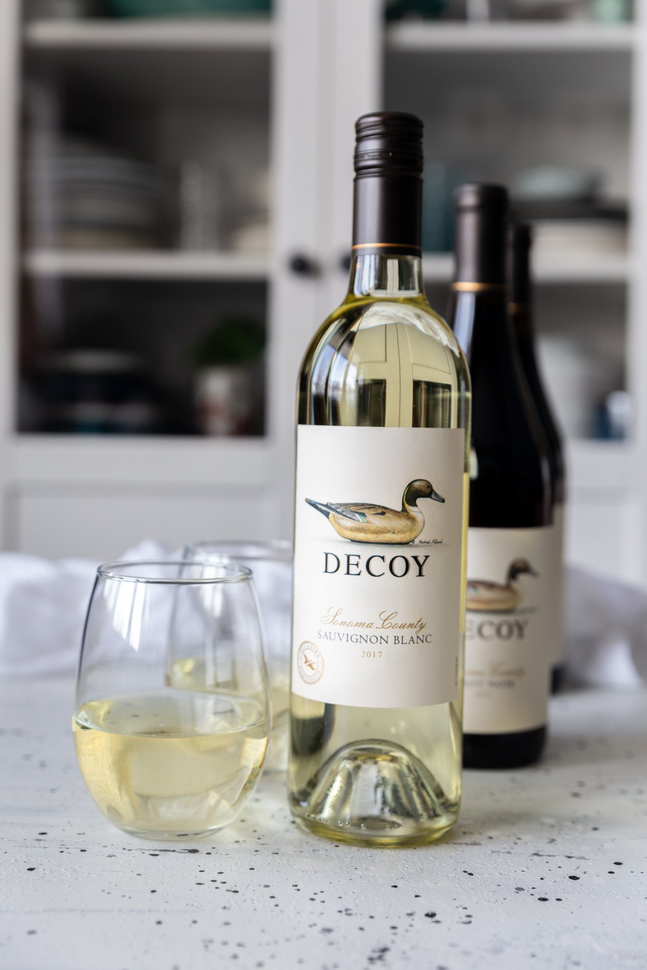 Bottles of Decoy Wine and glasses with wine in them.