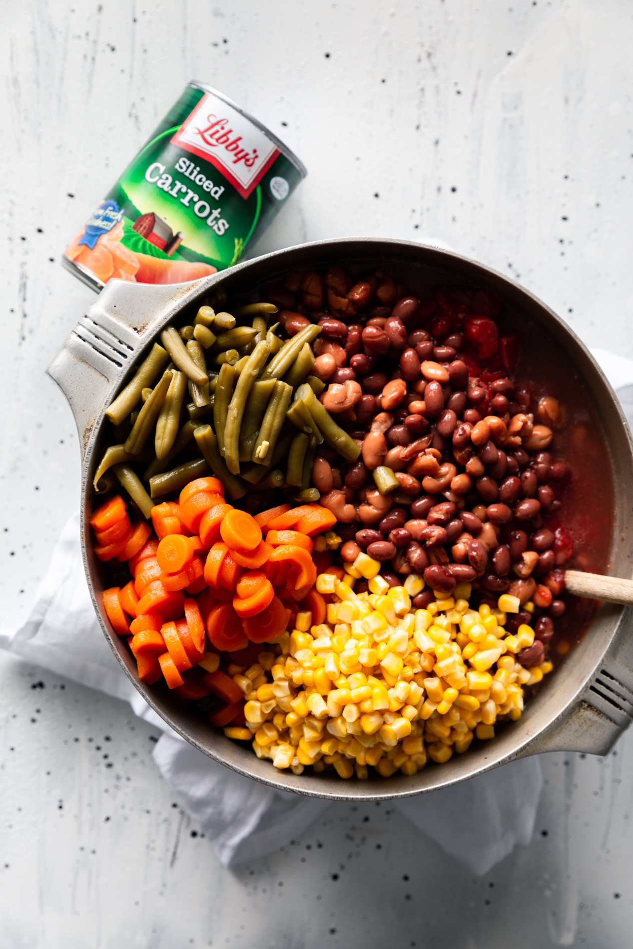 overhead view of a large pot of easy one pot taco stew with visible piles of beans, green beans, carrots, and corn.