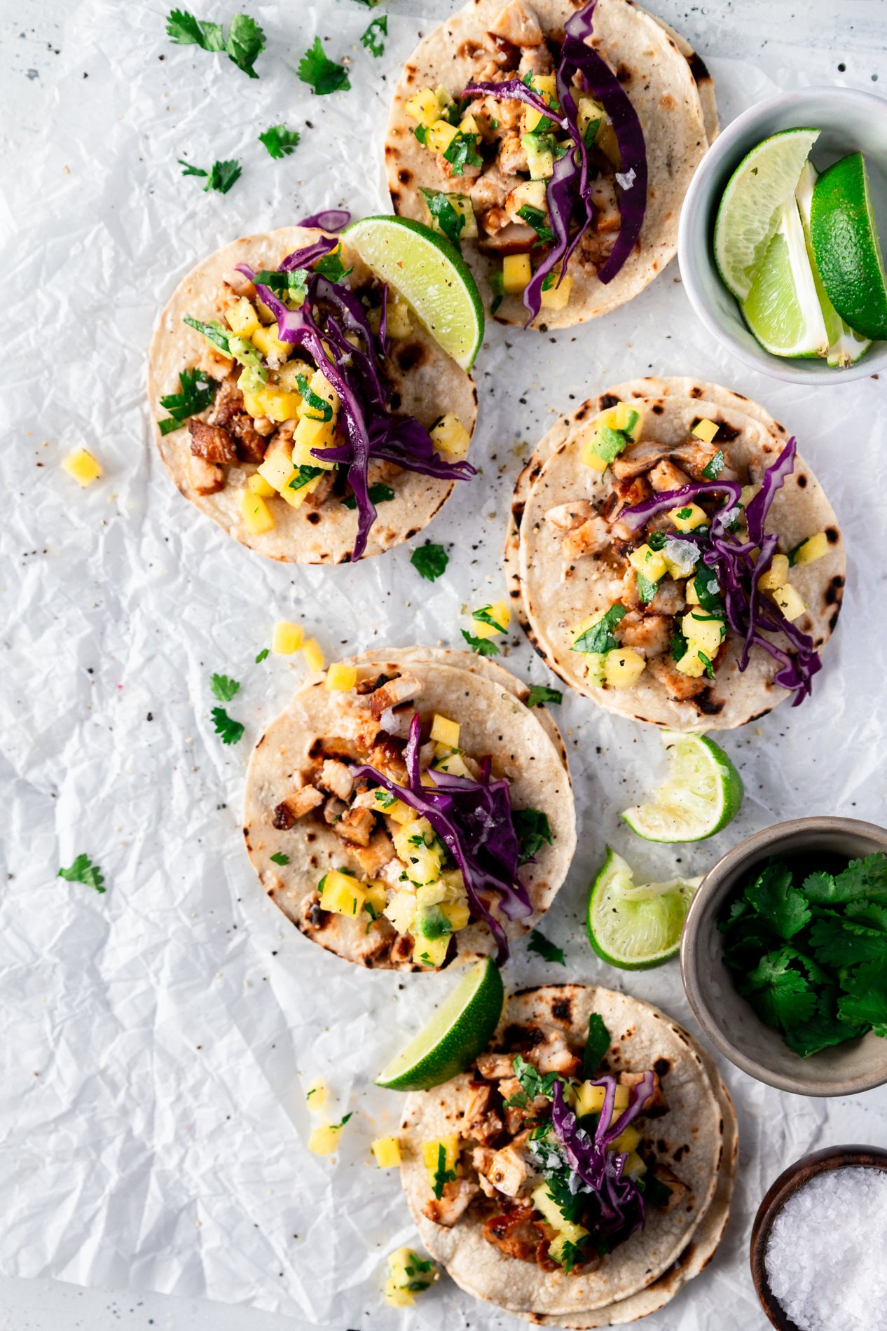 overhead view of five hawaiian huli huli chicken tacos with pineapple, mango, and avocado salsa. fresh limes are scattered around the tacos, as well as chopped cilantro.