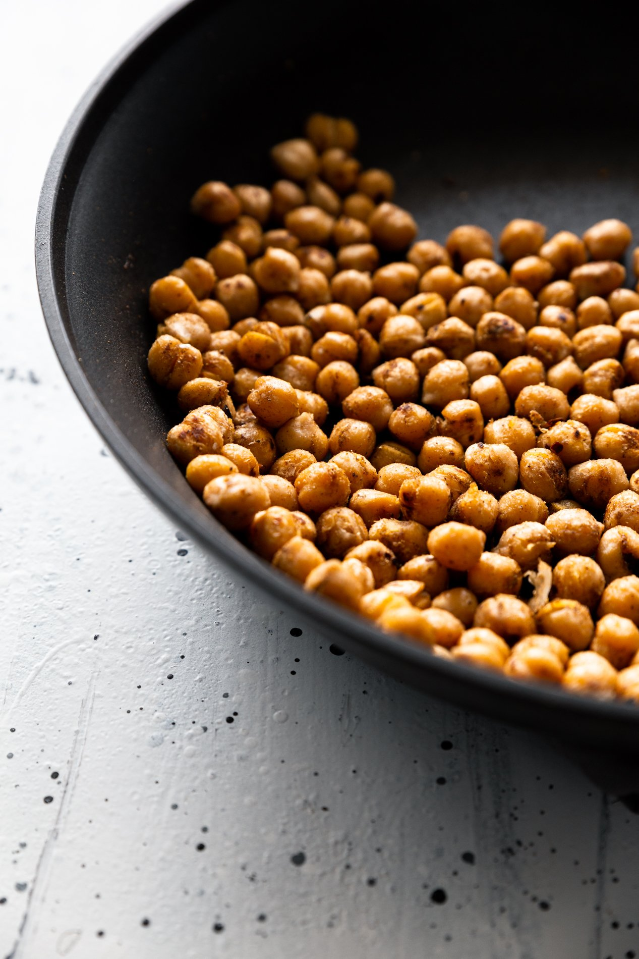 side view of a skillet with pan-roasted chickpeas in it.