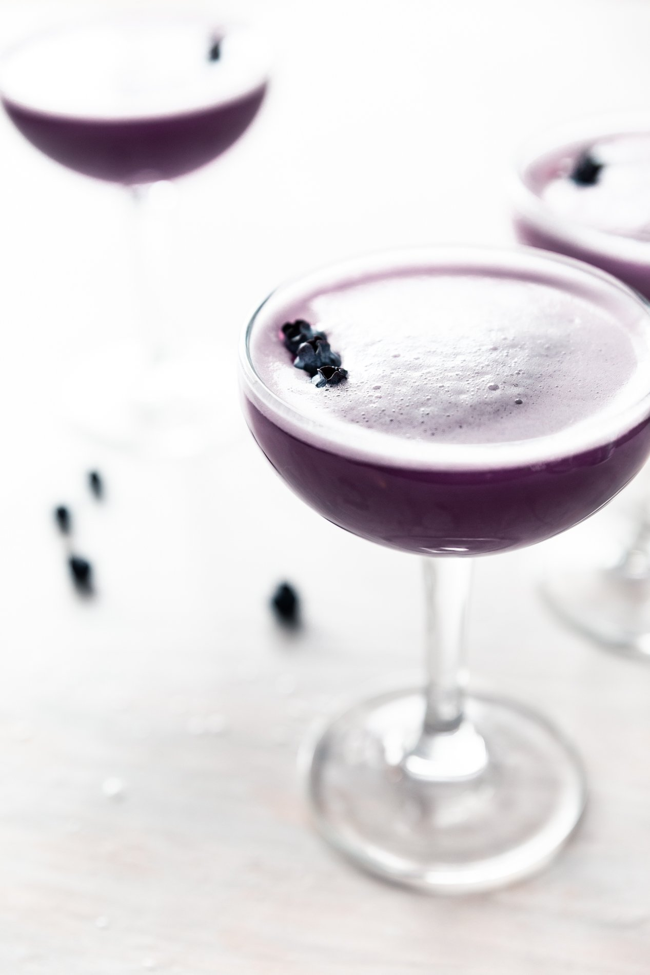 side view of bluberry clover club cocktails garnished with fresh blueberries by minnesota food blogger asimplepantry