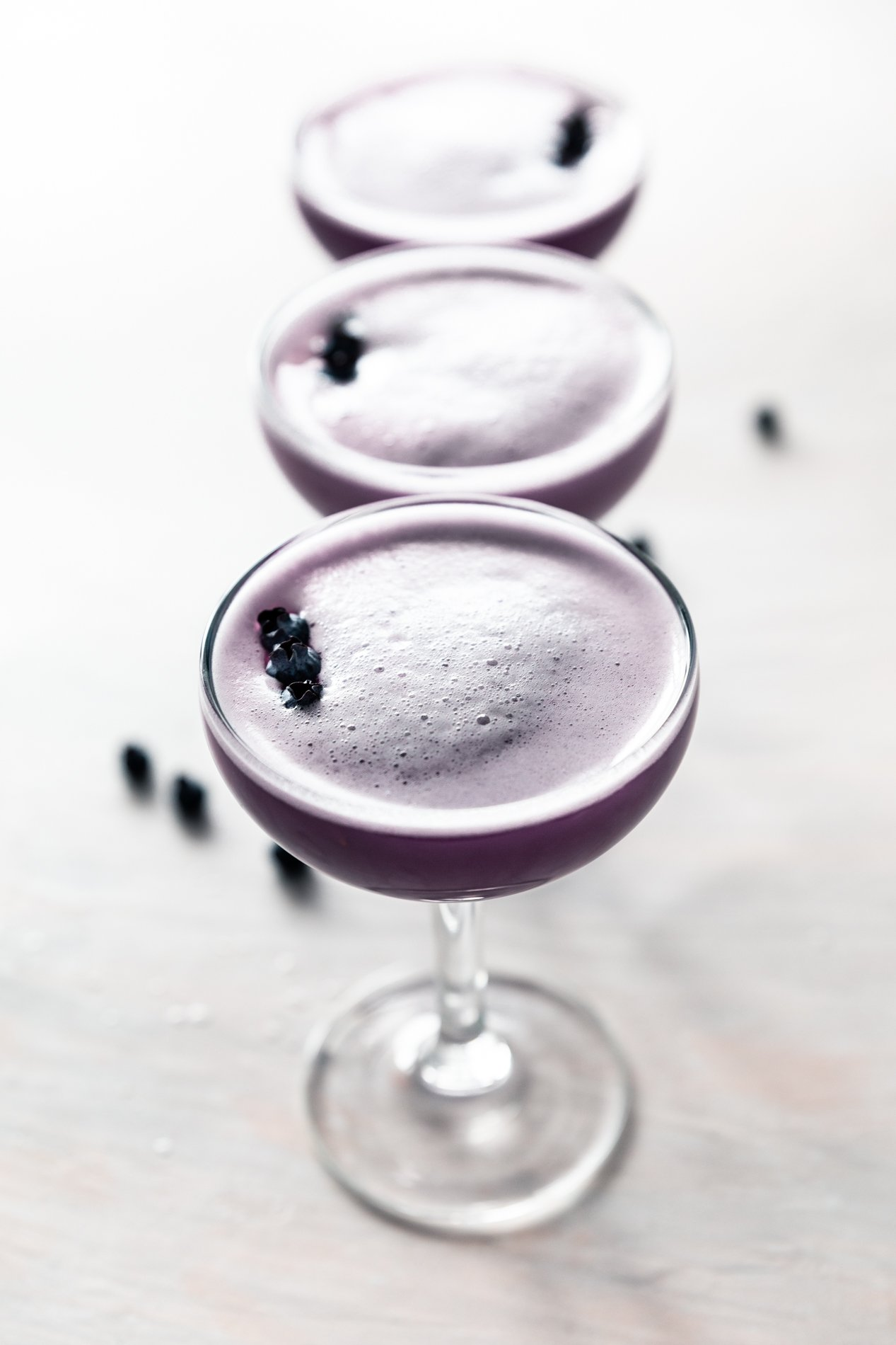 side view of a row of blueberry clover club cocktails by minneapolis food blogger asimplepantry