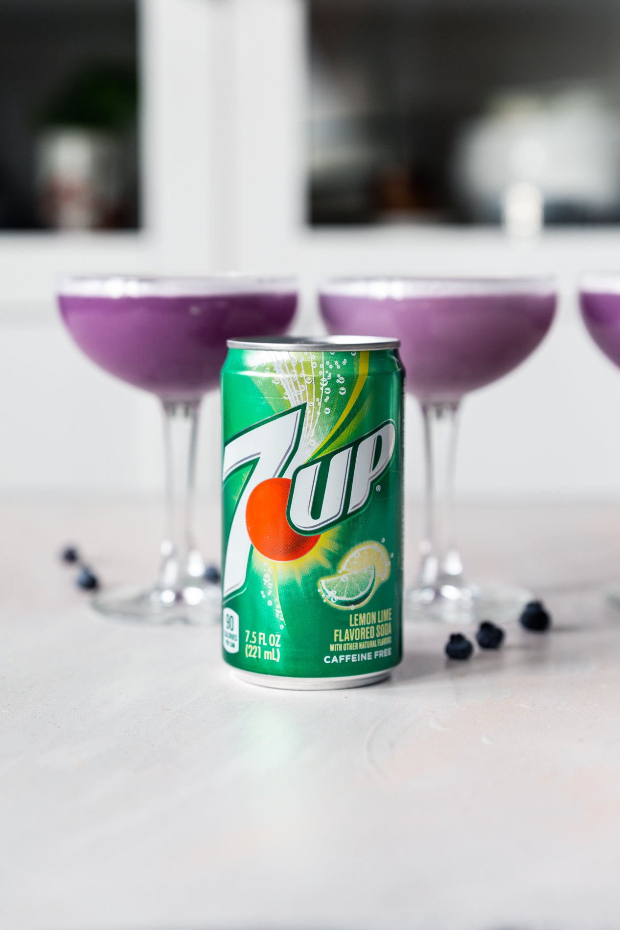 side view of a row of blueberry clover club cocktails with a 7up in front