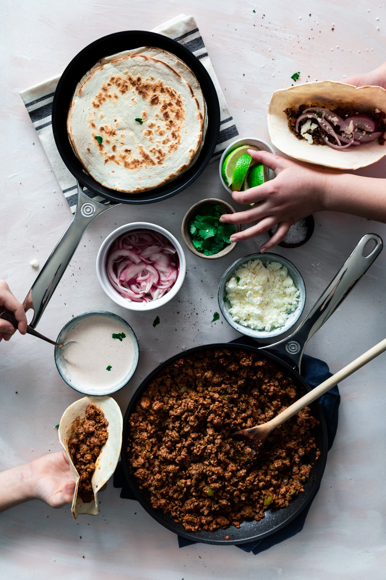 overhead view of two hands dishing out weeknight pork carnitas tacos into tortillas with small bowls of garnishes in the center, by minneapolis food blogger a simple pantry