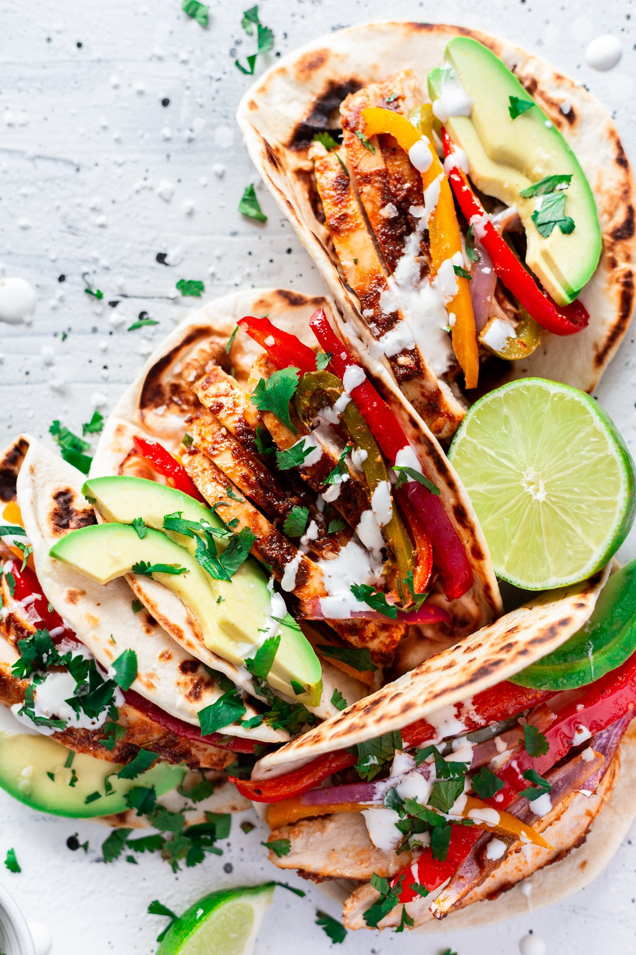 overhead view of chipotle sheet pan chicken fajita tacos topped with sour cream, avocado, cilantro, and lime juice