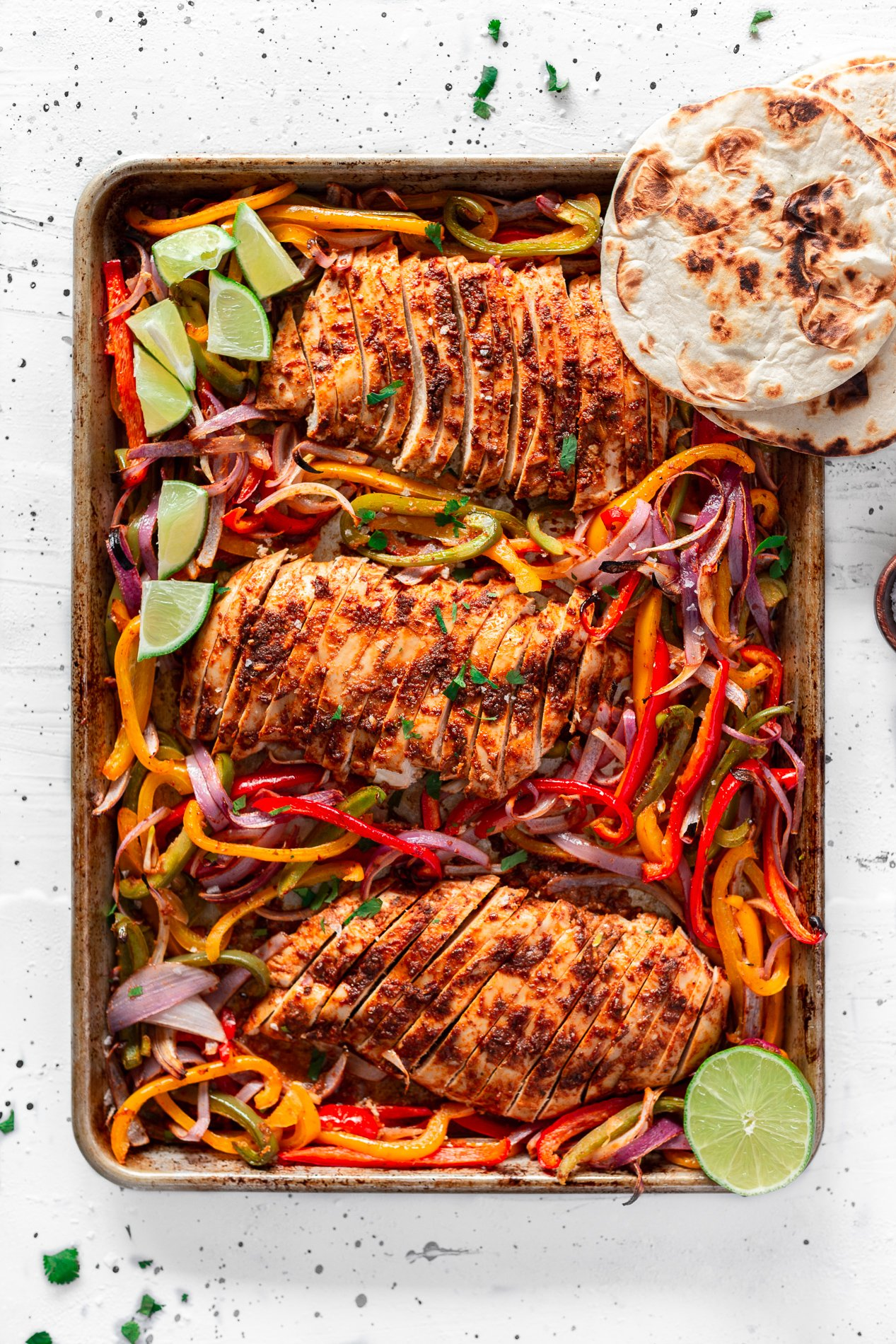overhead view of chipotle sheet pan chicken fajitas after being cooked in the oven, with sliced chicken breast, toasted tortillas, and lime wedges