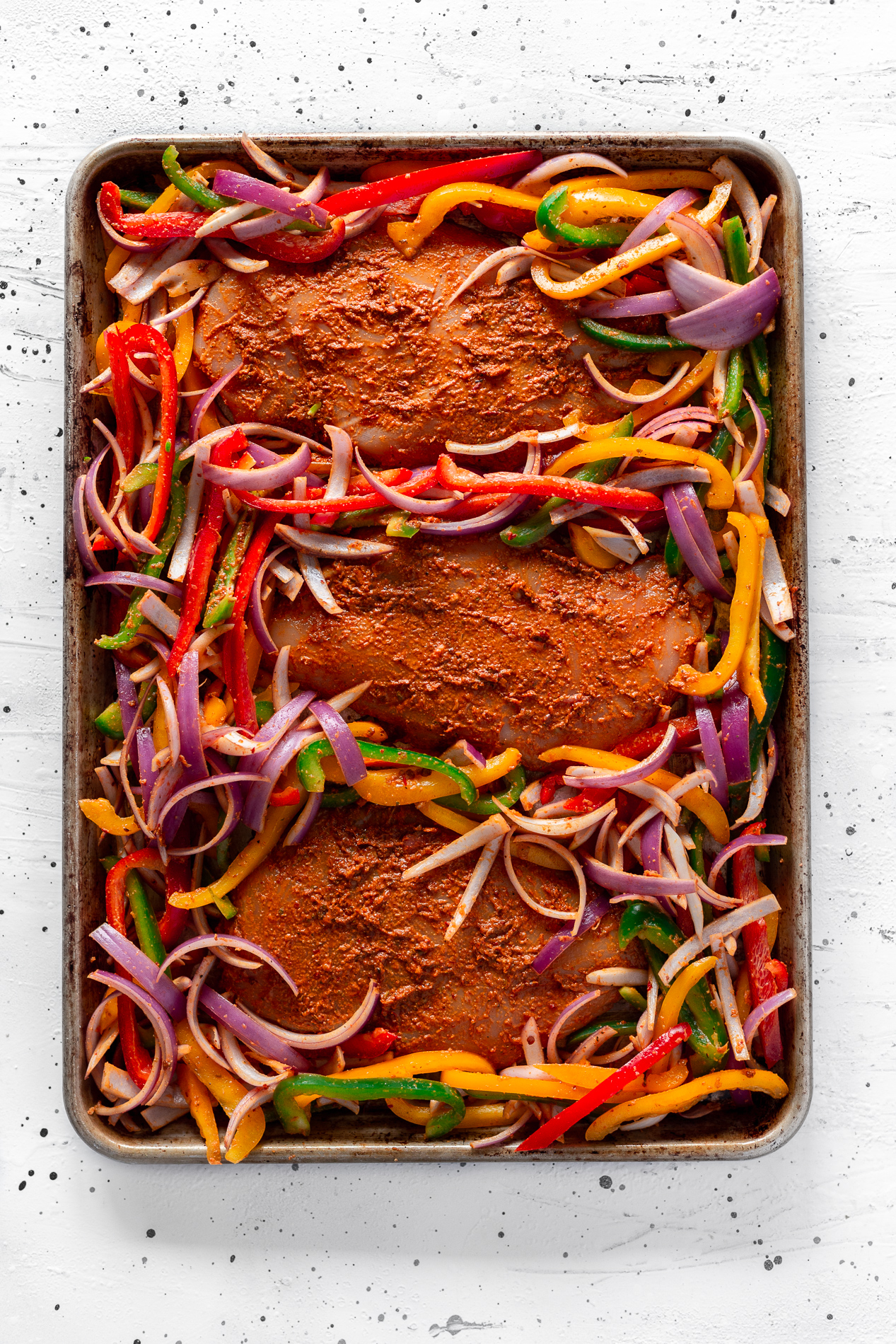 overhead view of chipotle sheet pan chicken fajitas before going in the oven.
