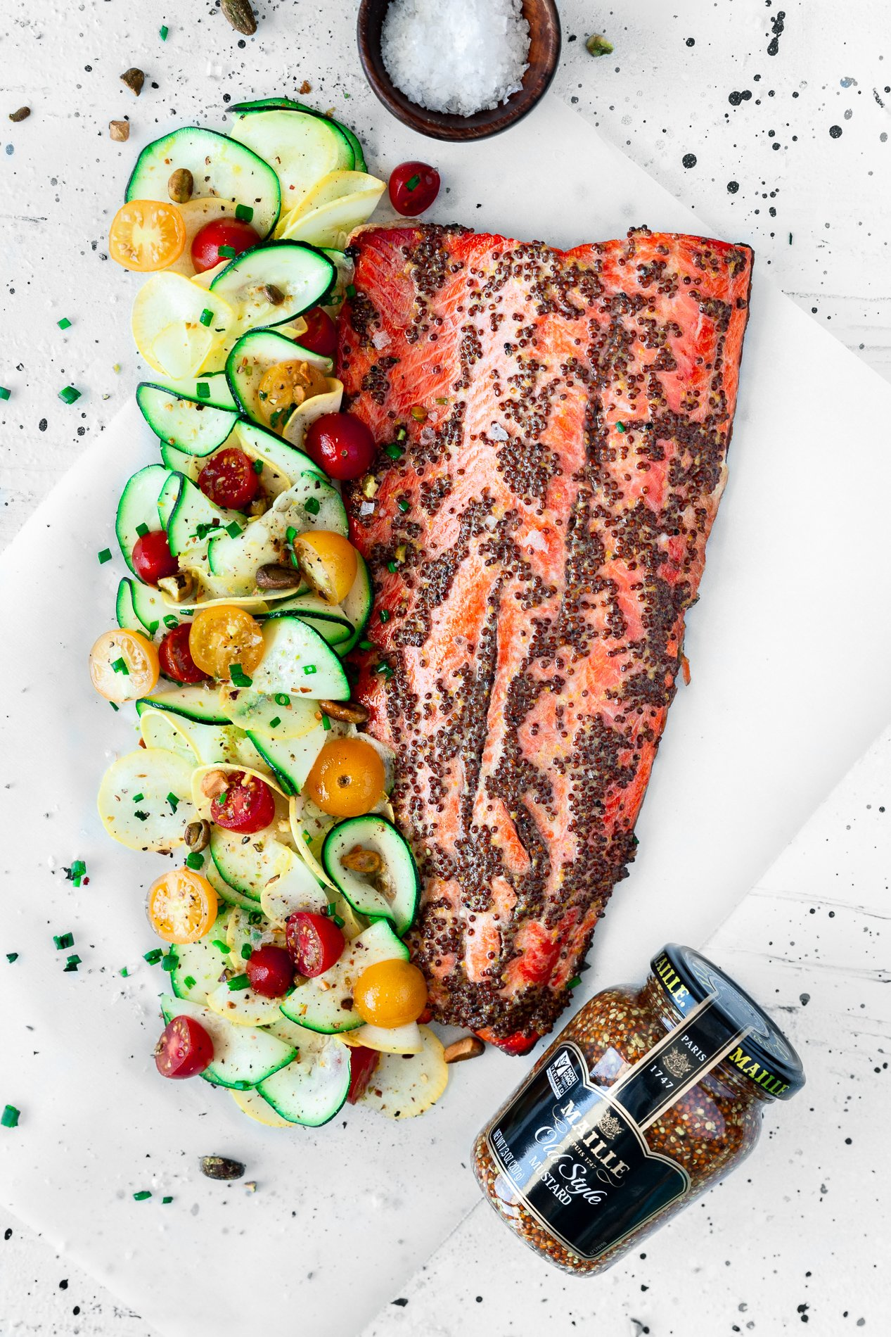 overhead view of mustard salmon with citrus squash salad and a jar of maille mustard