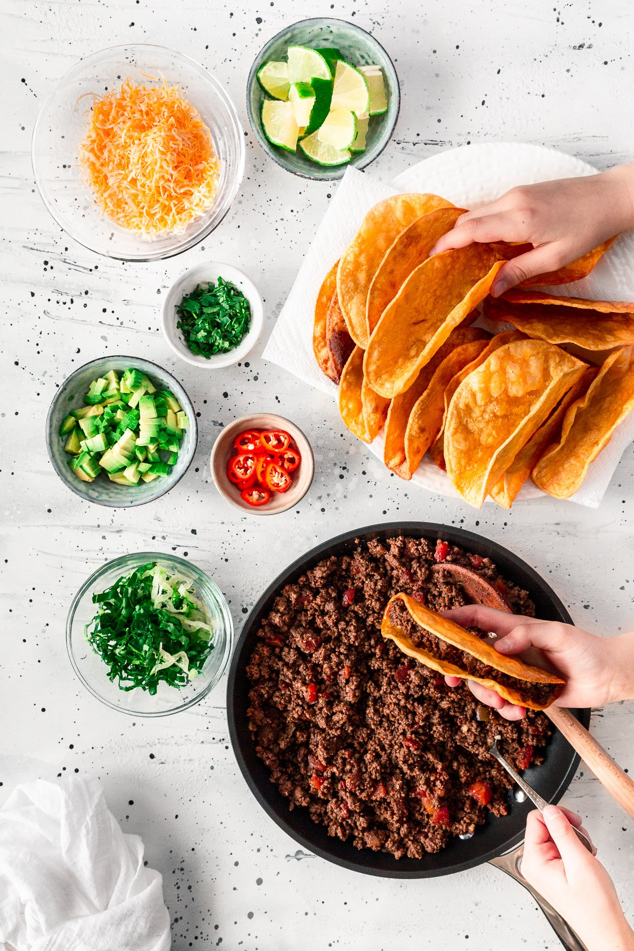 overhead view of crispy beef tacos being plated by two sets of hands, with toppings in small bowls surrounding them. by minnesota food blogger asimplepantry