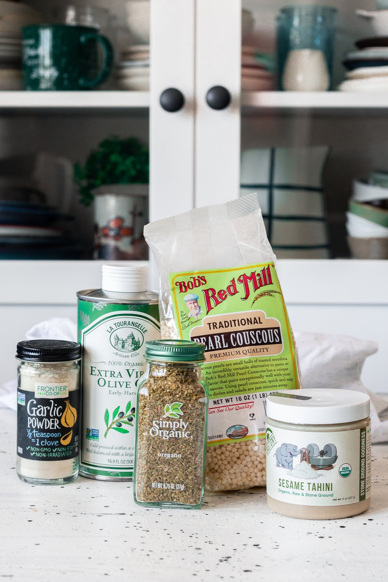 straight forward view of jars of garlic powder and oregano, a container of extra virgin olive oil, a bag of dried pealed couscous, and a jar of tahini