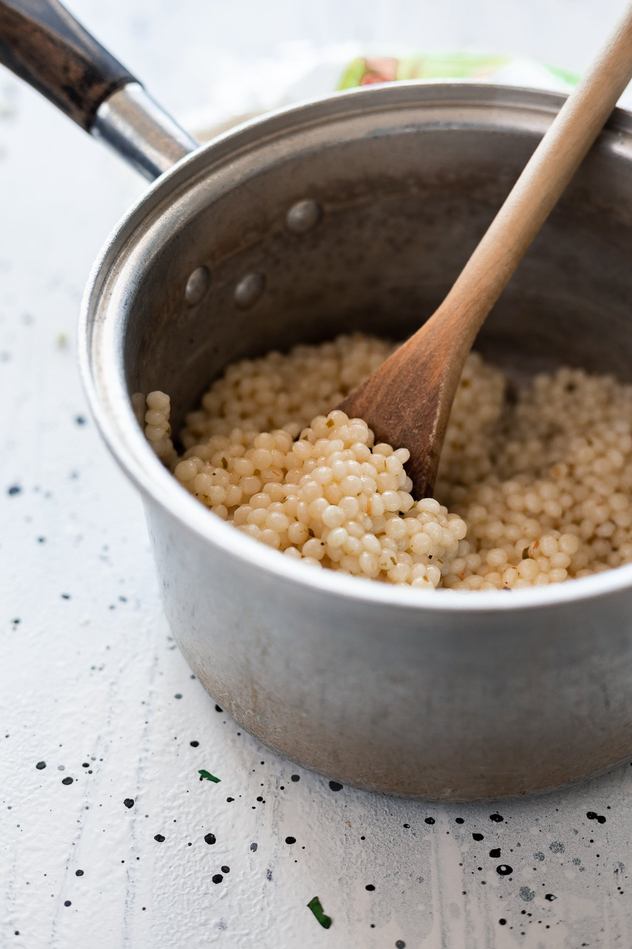 side view of a pot of pearled couscous with a wooden spoon inside it