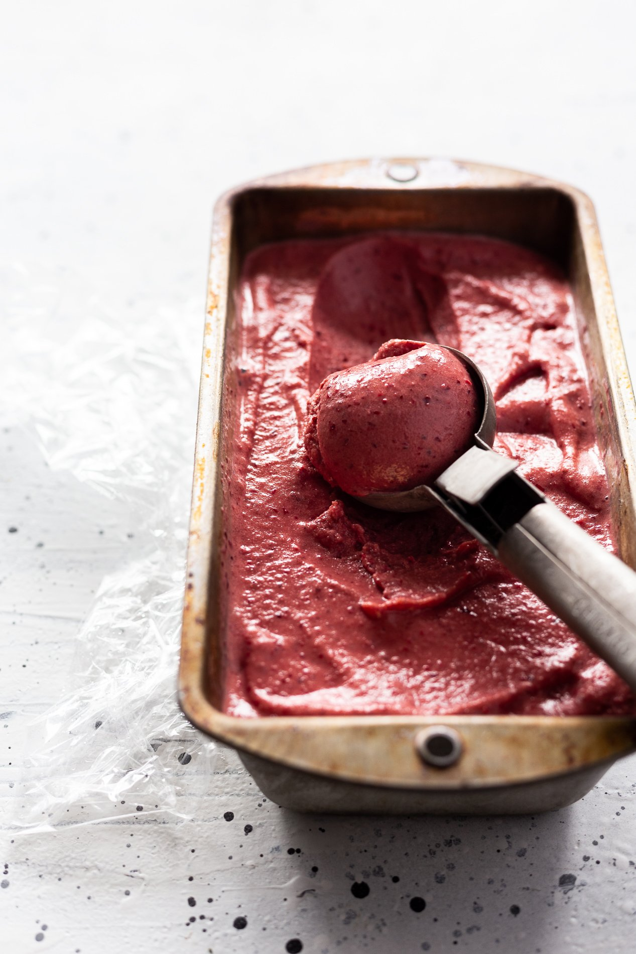 angled view of a tin of instant cherry ice cream with a scoop taken out of it