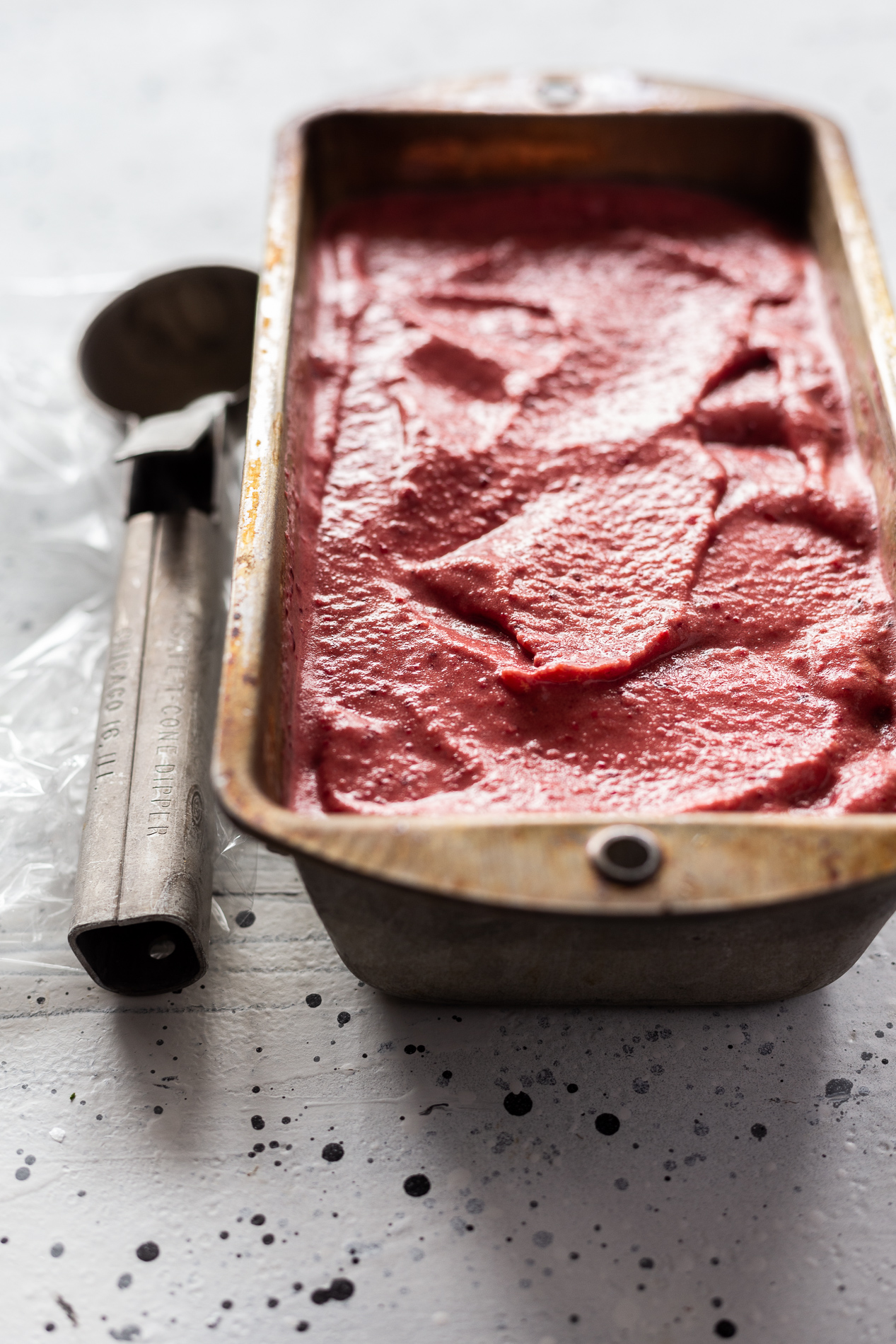 angled view of a tin of instant cherry ice cream with a scoop sitting beside it