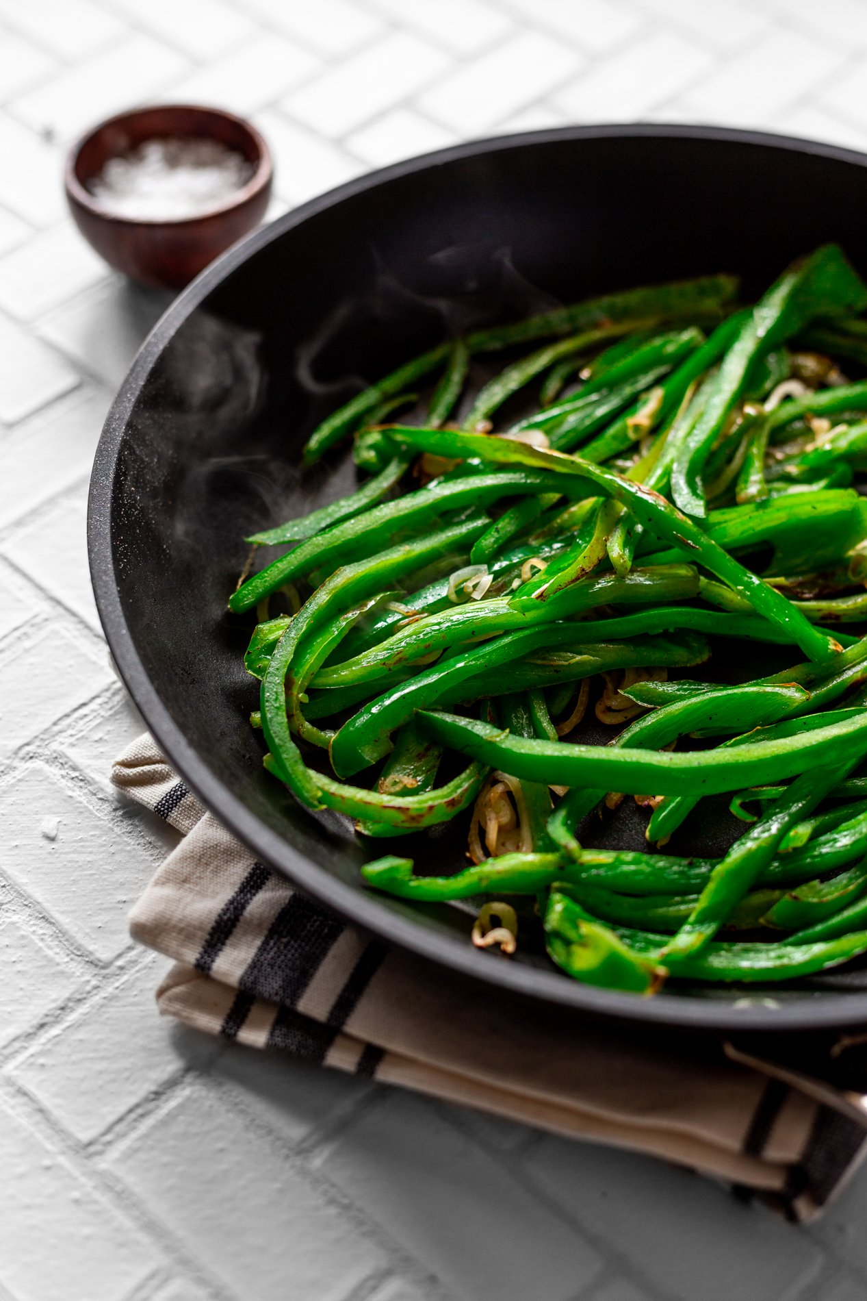 angled view of poblano peppers and shallots sauteed in a skillet, with steam swirling off the peppers